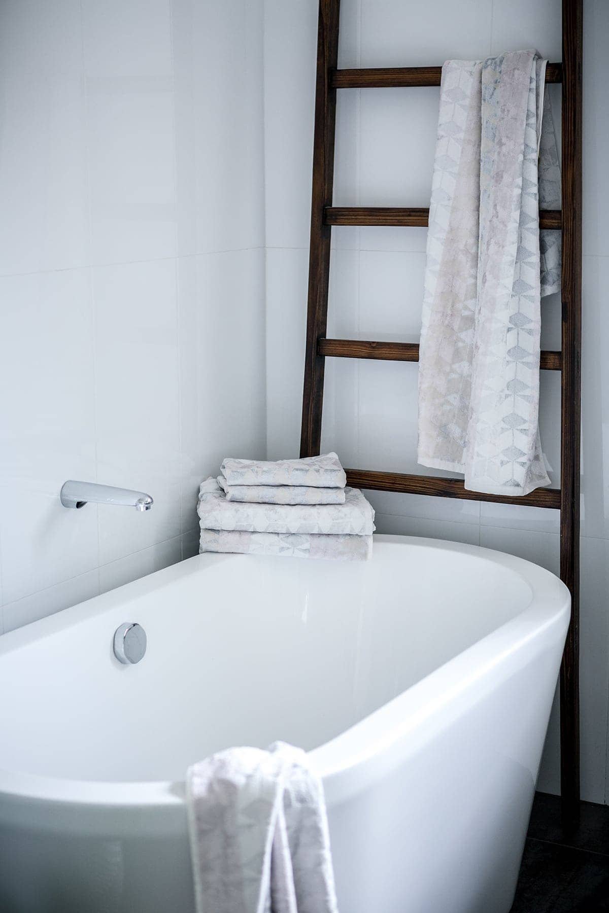 bathroom with white freestanding bath tub and dark brown rustic ladder