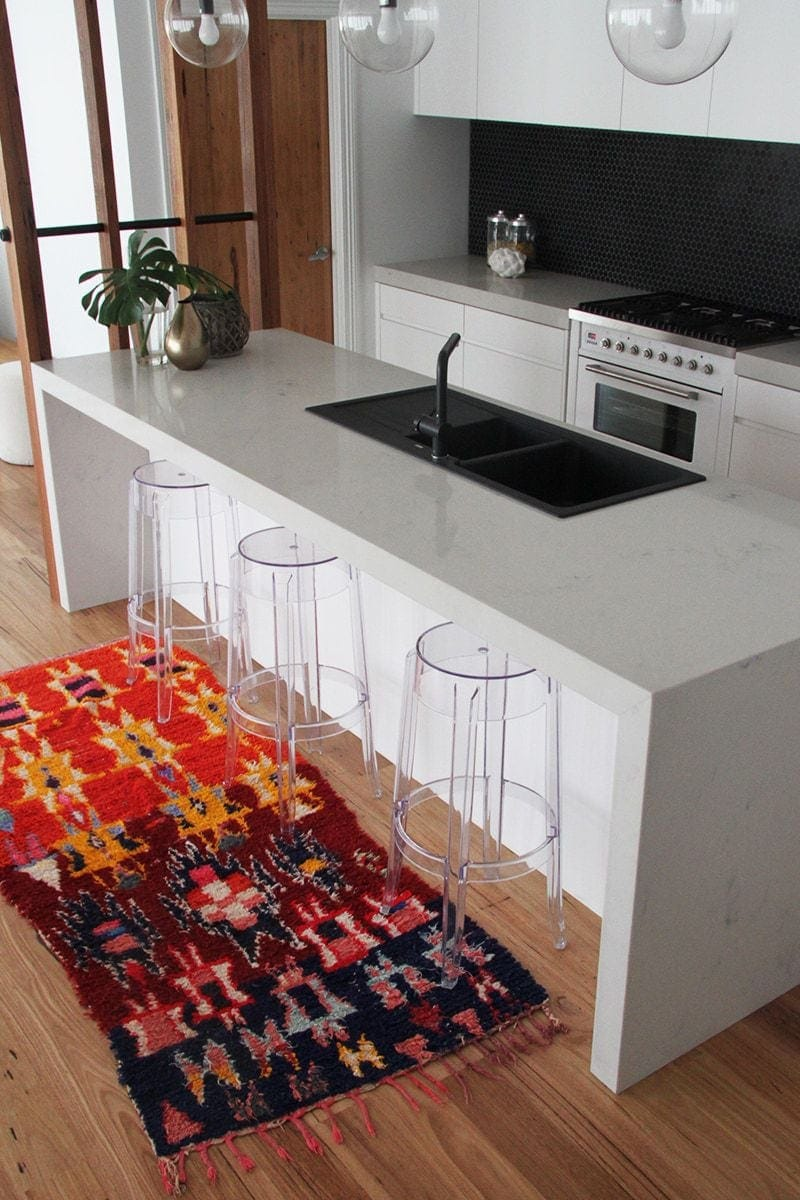 black and red moroccan rug on kitchen floor with plastic ghost stools