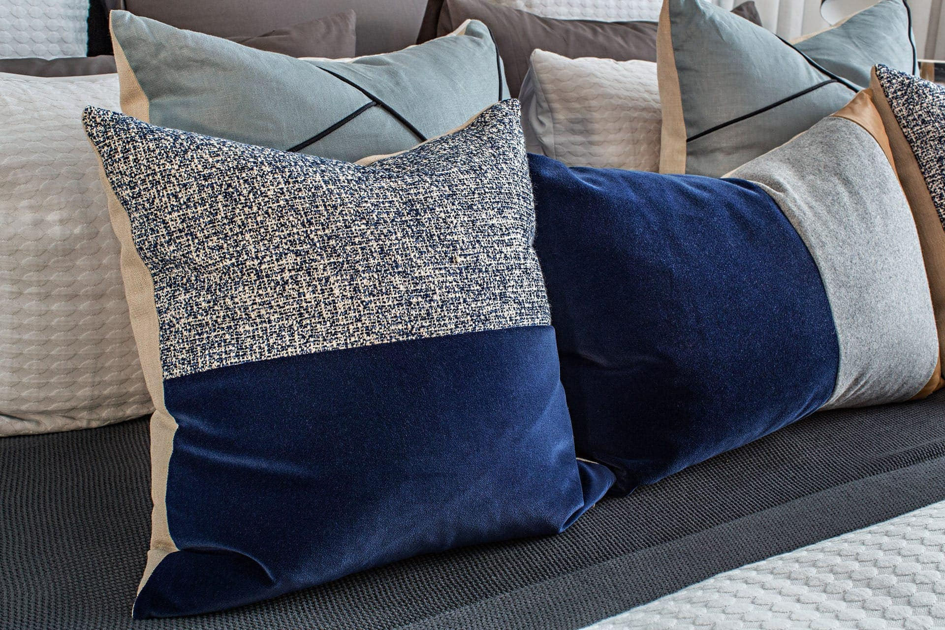 blue and grey velvet cushions on bed in modernist home from metricon
