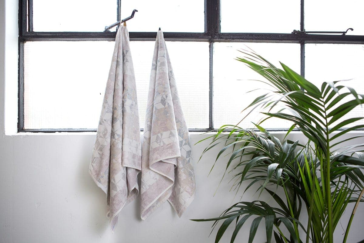 blush and white pattern towels hanging in warehouse style bathroom with fern