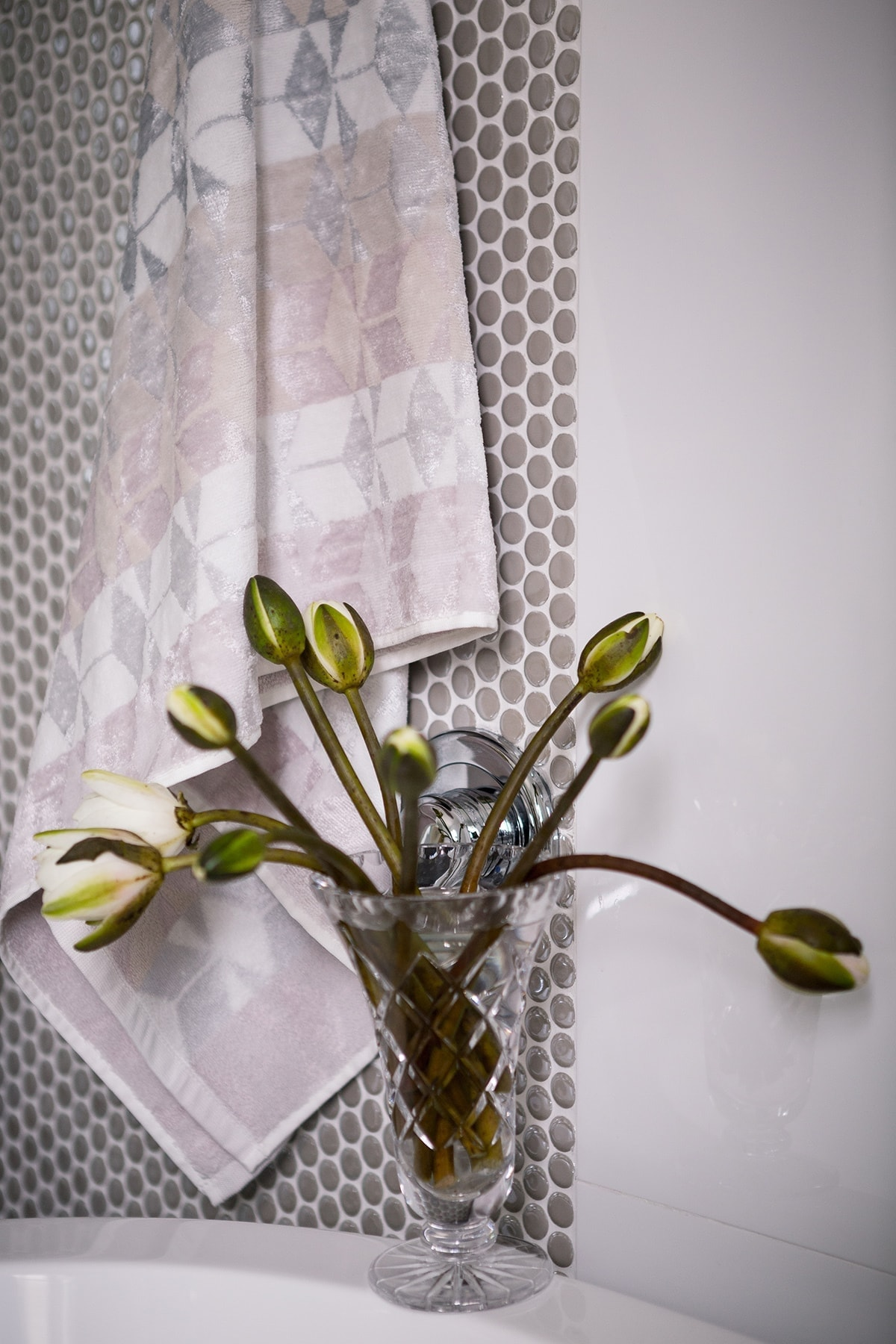 closed flower buds in ornate glass vase on top of freestanding bath