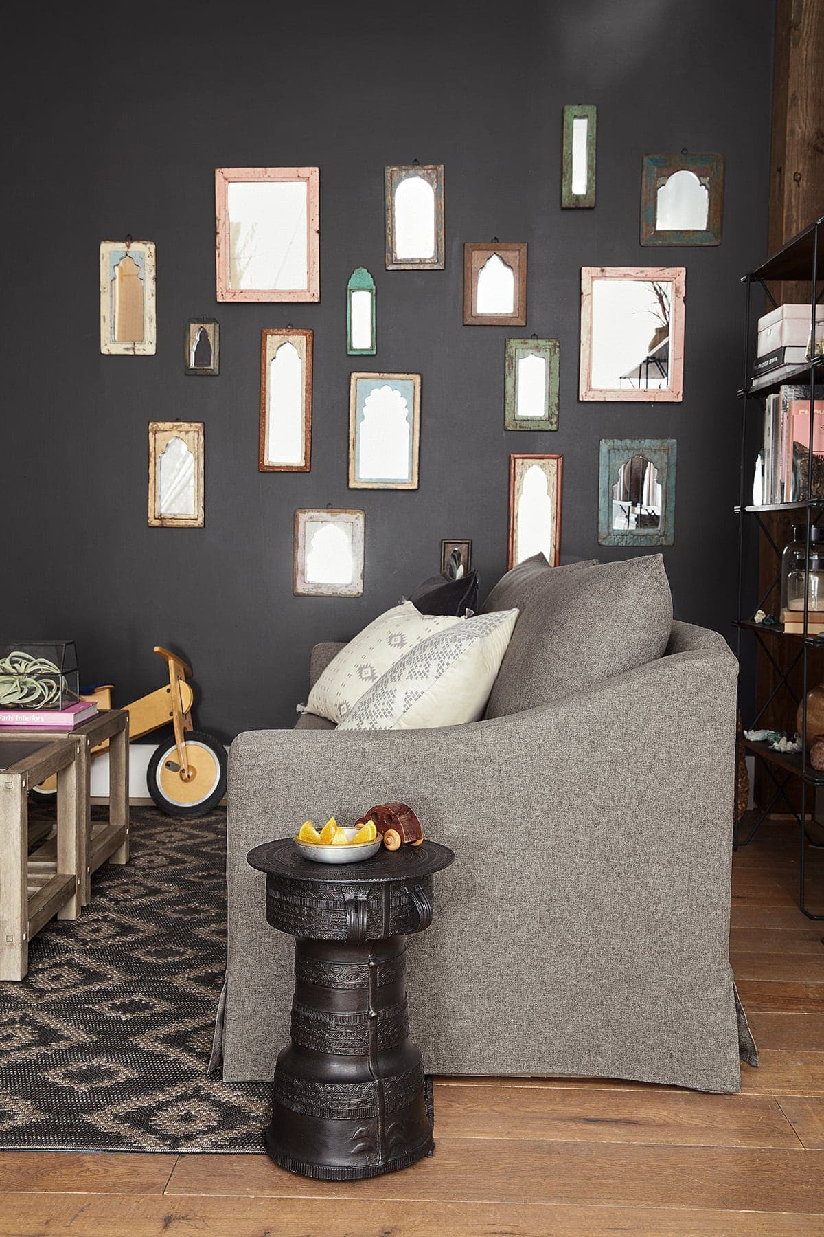 cluster of small mirrors on black feature wall in living room in moroccan style