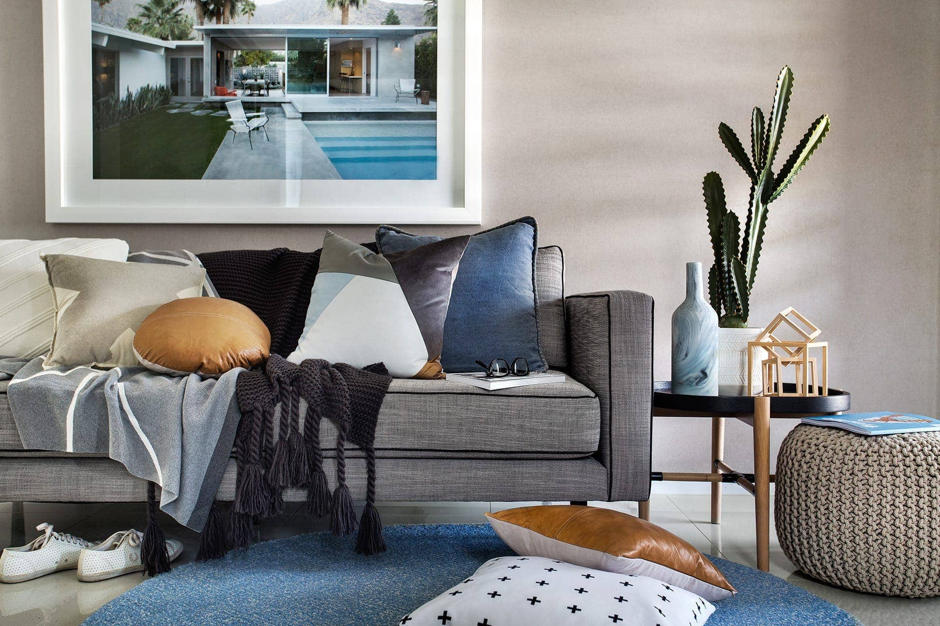 coastal living room with grey sofa and blue and tan cushions from metricon
