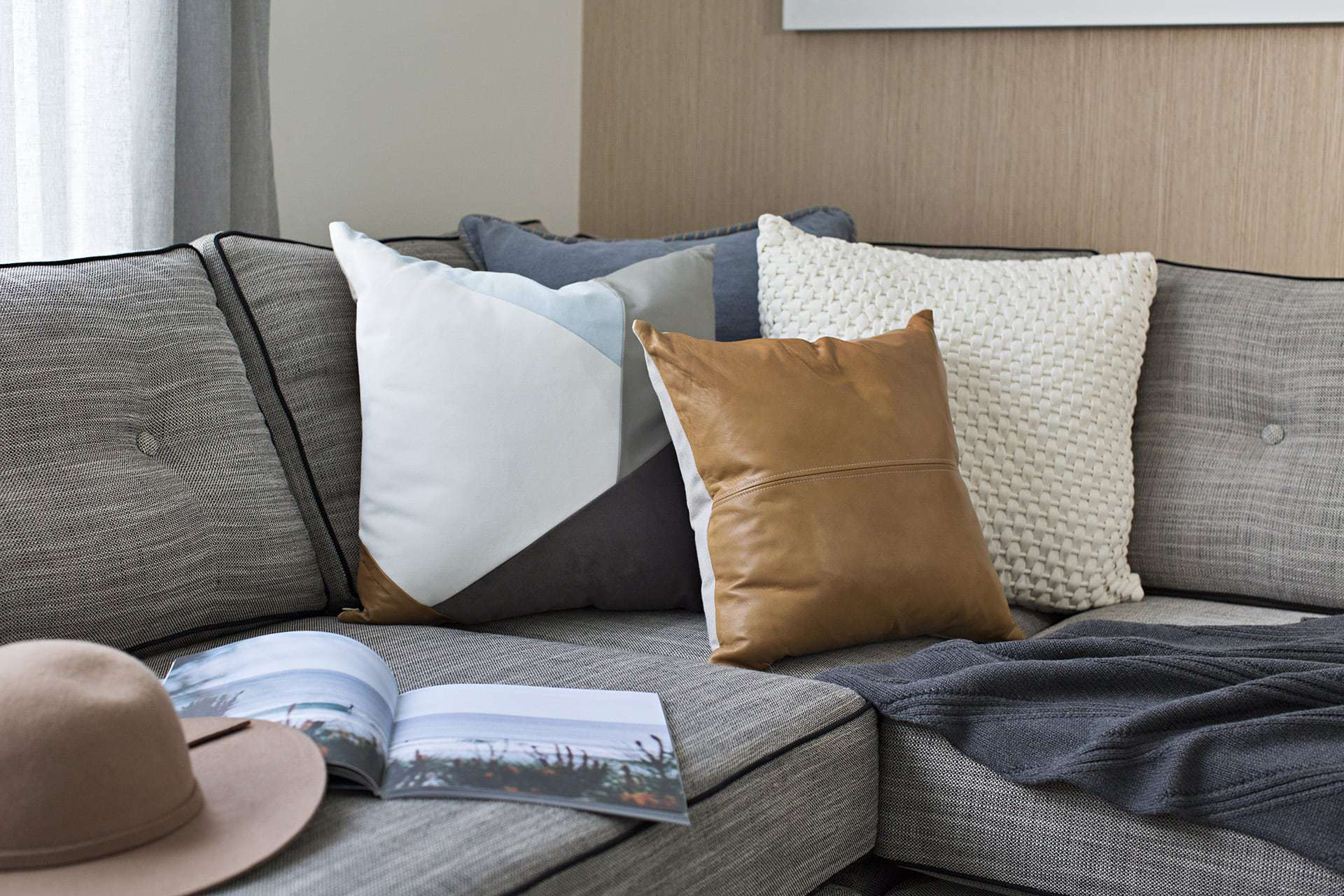 grey tufted sofa with tan leather cushion and blue and white geometric cushion