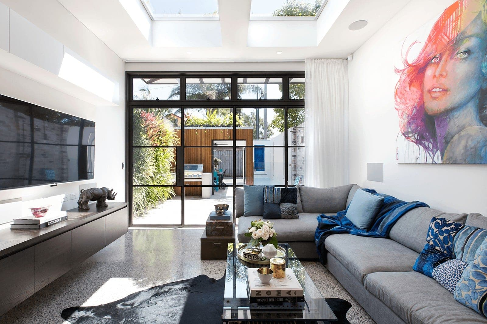 living room with concrete floor and grey sofa with blue cushions from vault interiors