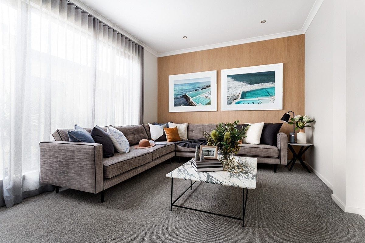 living room with grey sofa and navy and tan cushions in metricon display home