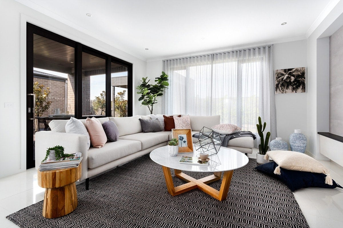 living room with white sofa and pink and maroon cushions from metricon display home