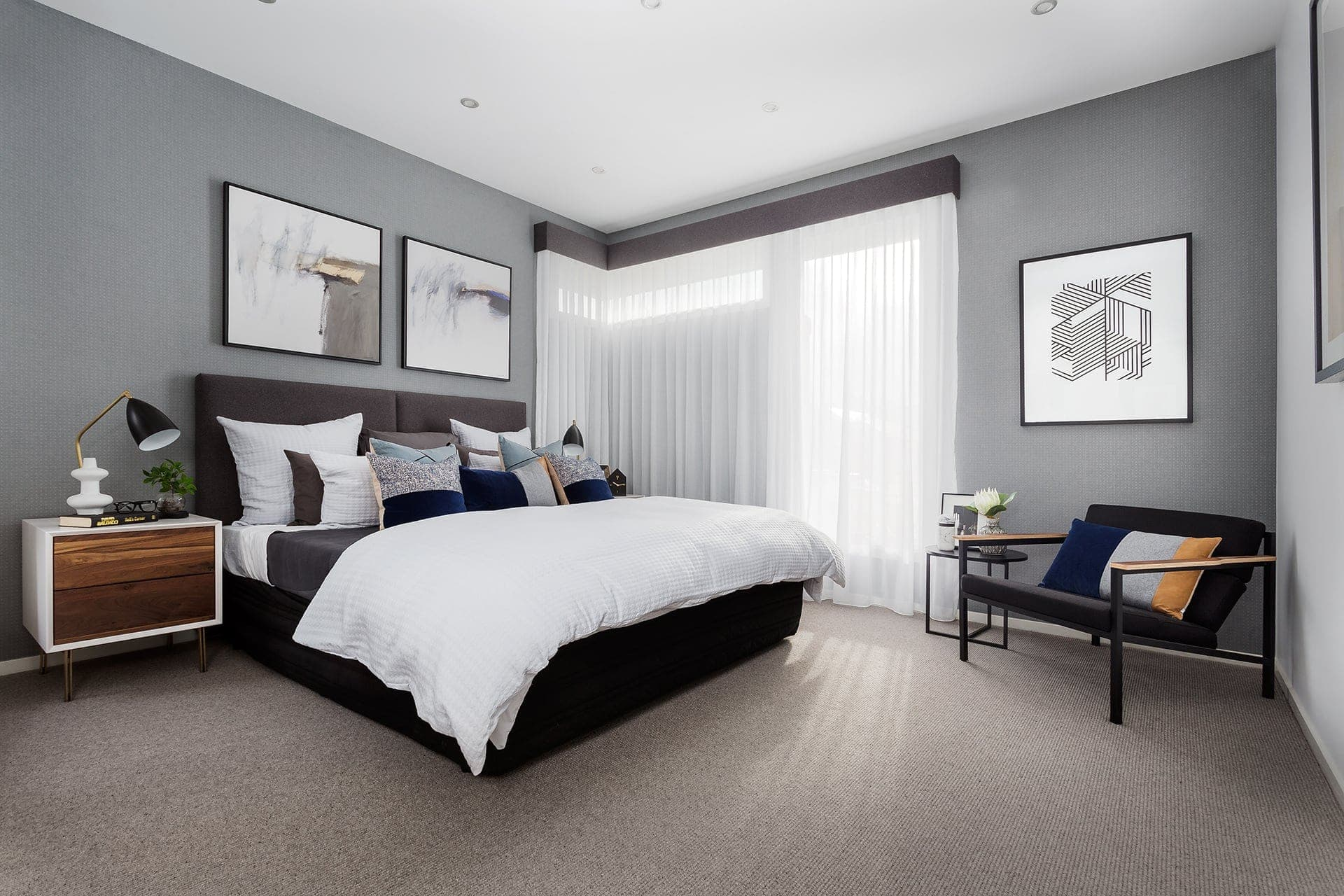 master bedroom with olive polka dot wallpaper and black armchair in corner from metricon