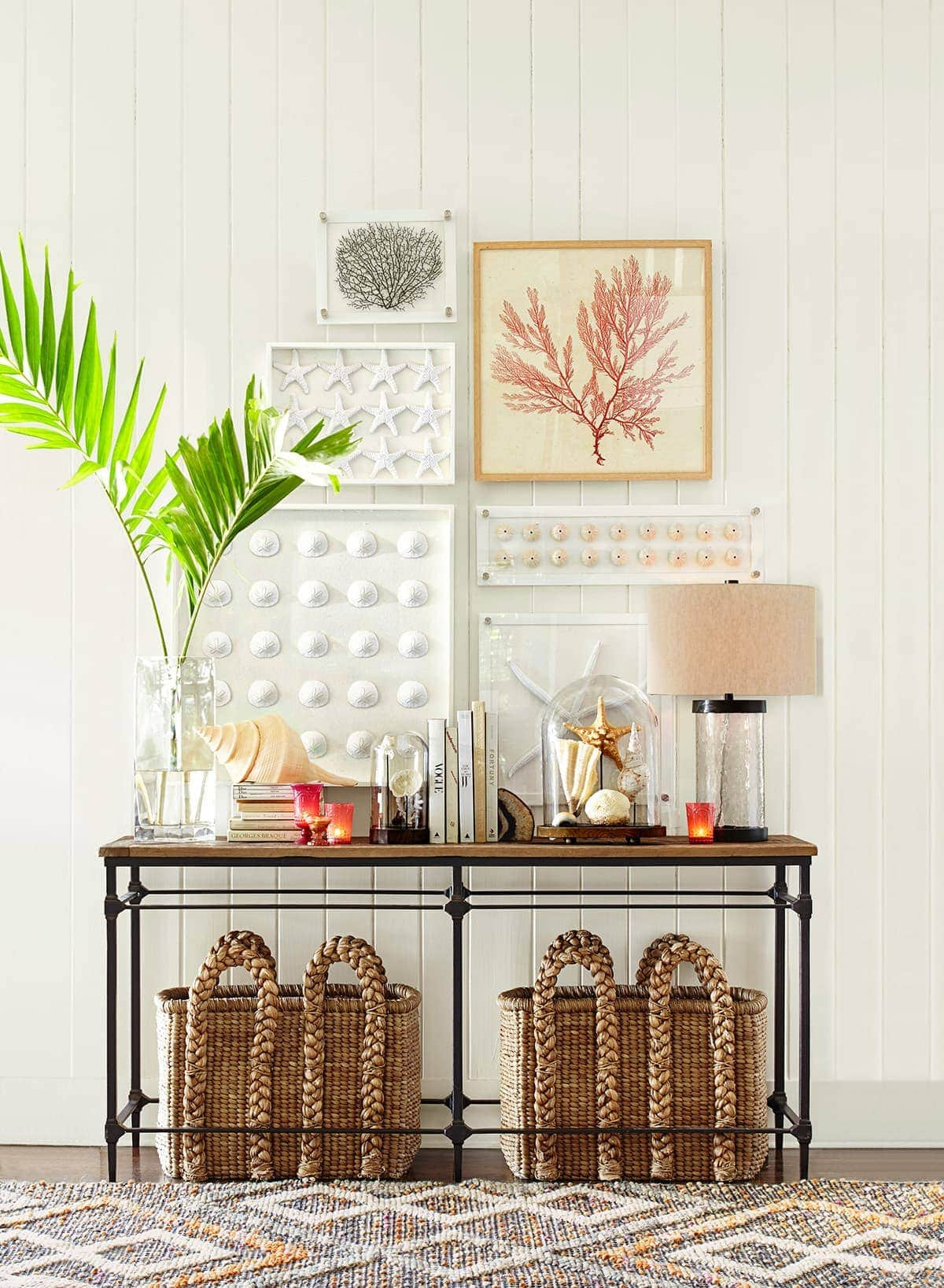 pottery barn entry table with wicker baskets underneath and coastal styling on top