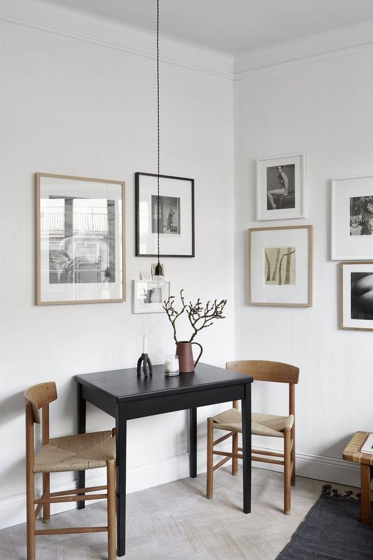 small dark brown dining table against wall with timber dining chairs and pendant hanging above