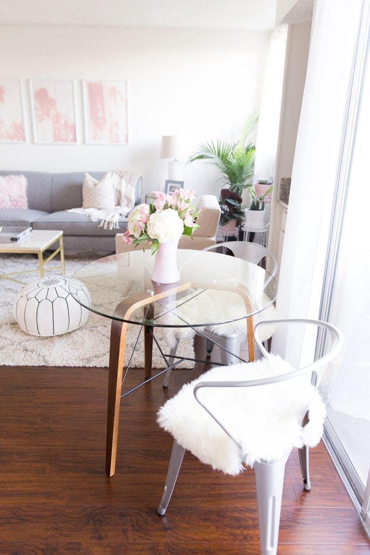 small round glass top dining table with metal chair and faux fur throw