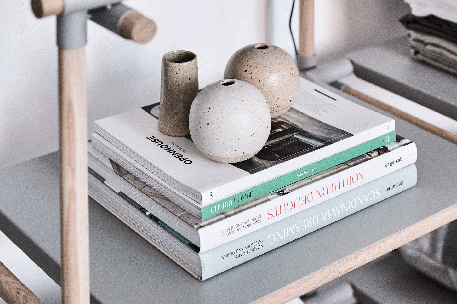 speckled handmade vessel on stack of books in bed showroom