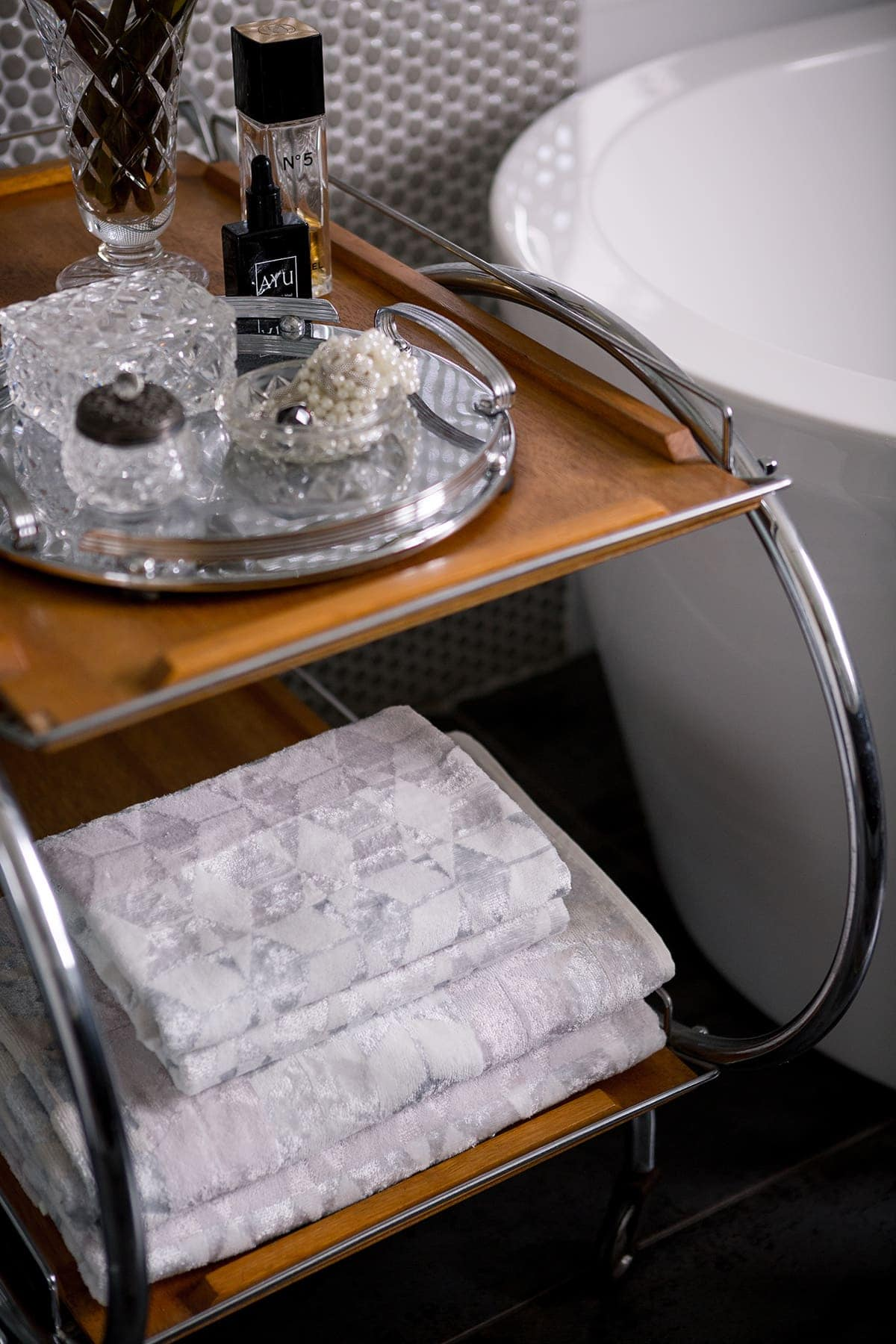 vintage table in bathroom with stack of towels on it