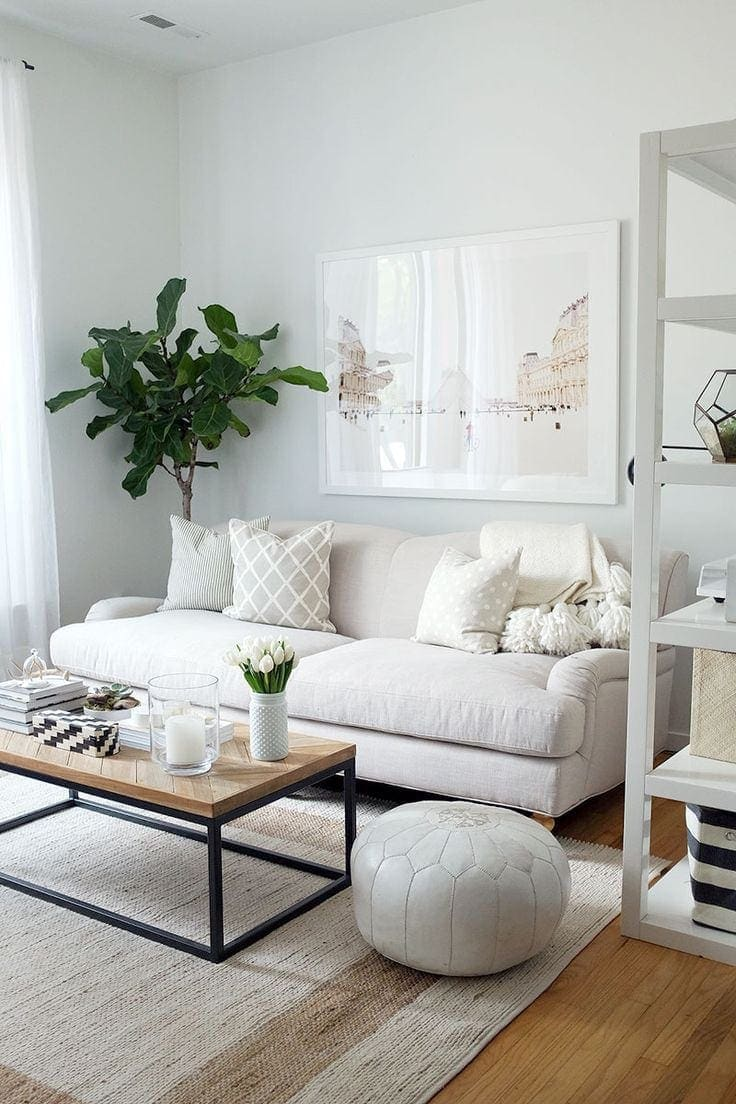 white coastal living room with white fabric sofa and white leather ottoman