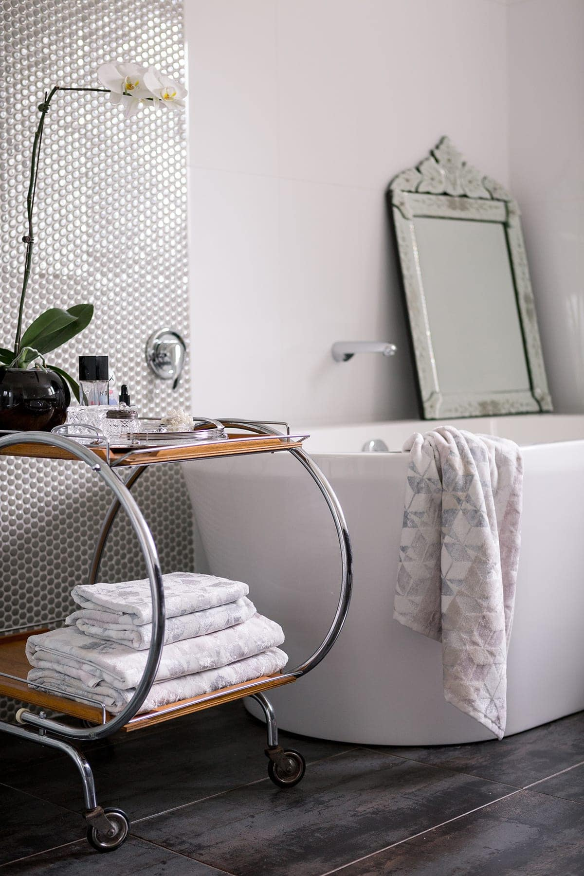 white freestanding bath tub with ornate white mirror leaning against wall