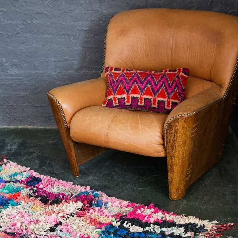 worn leather armchair with moroccan cushion and colourful moroccan rug from nouvelle nomad
