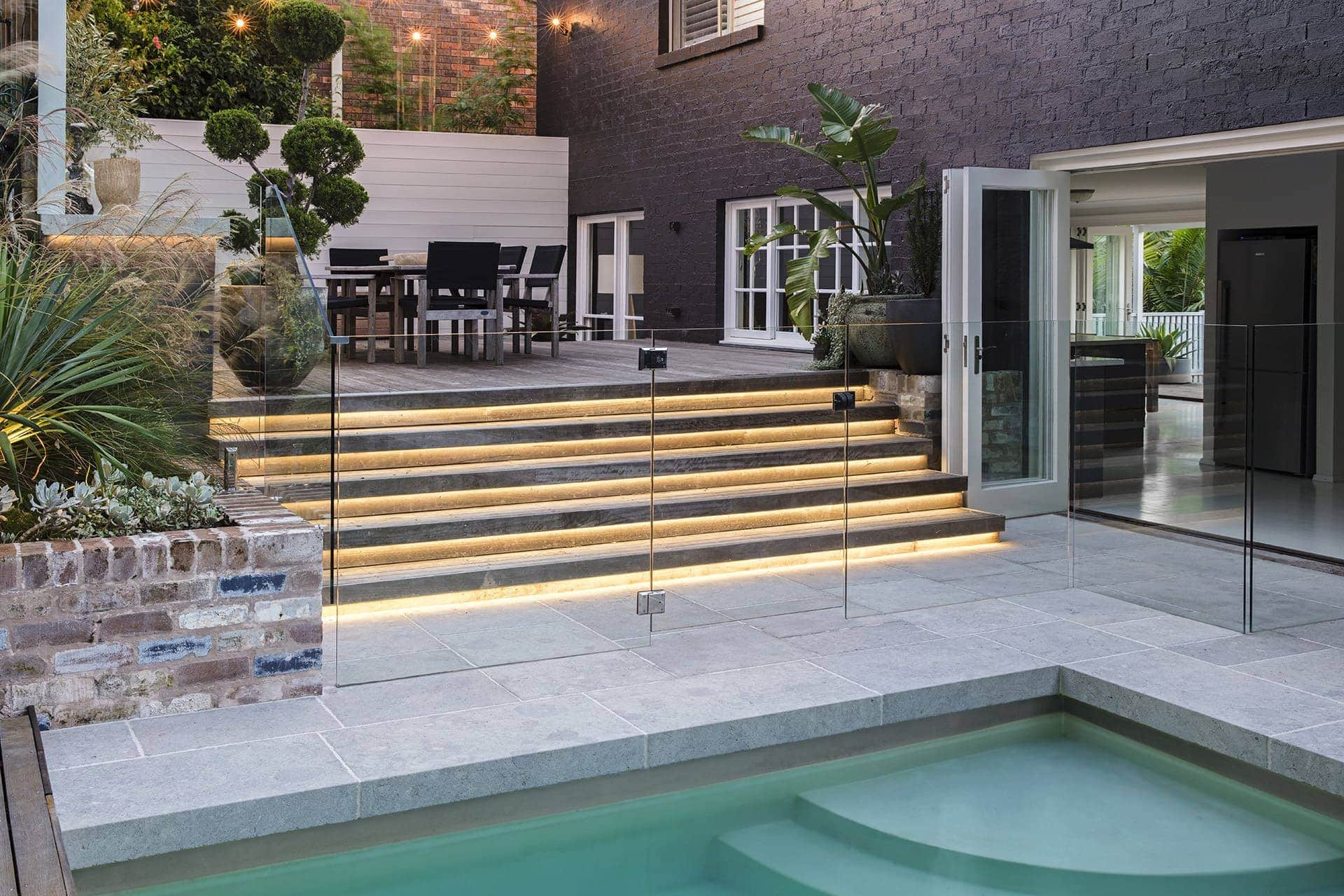 Strip lighting under stairs in pool area backyard