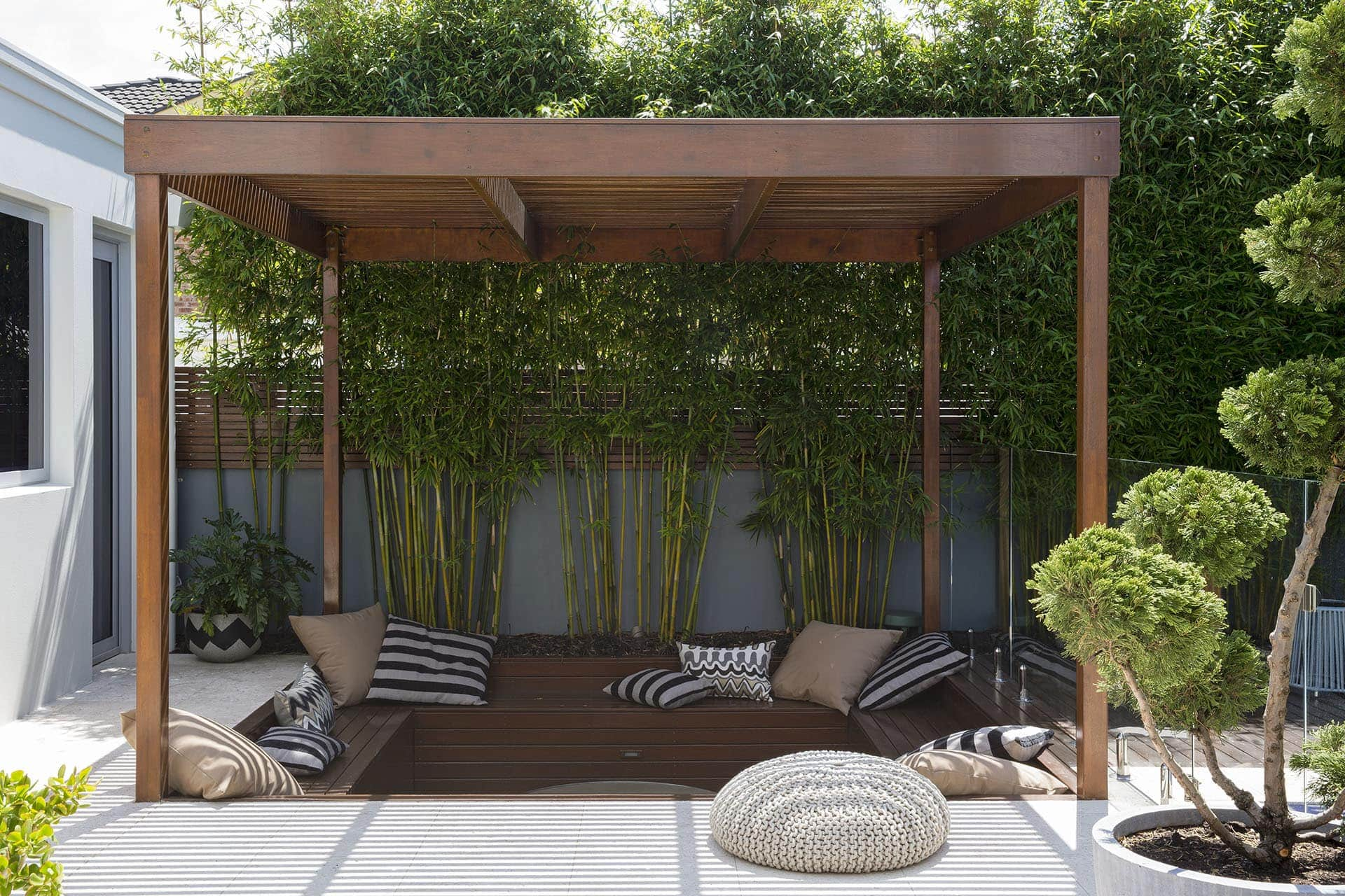 Sunken outdoor lounge area with timber benches and outdoor cushions