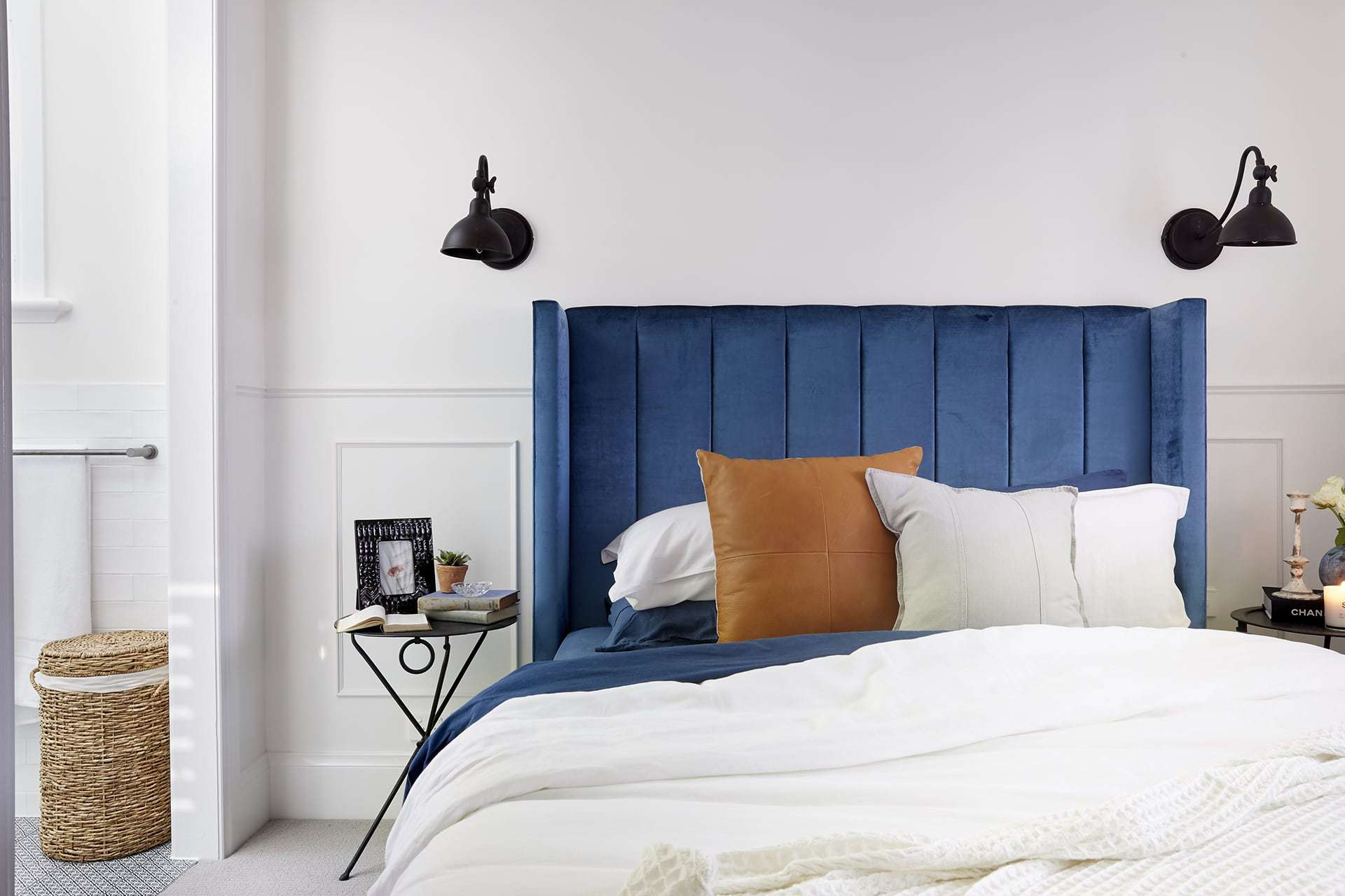 the block 2017 josh and elise guest bedroom blue velvet headboard and black wall sconces