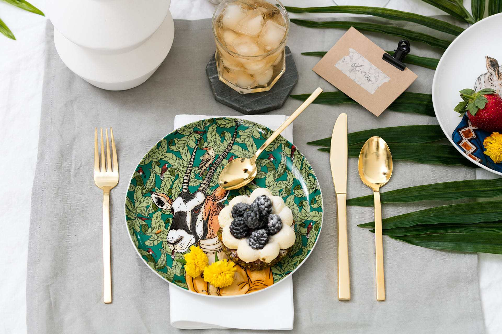west elm goat plate with gold cutlery set and palm leaf on table