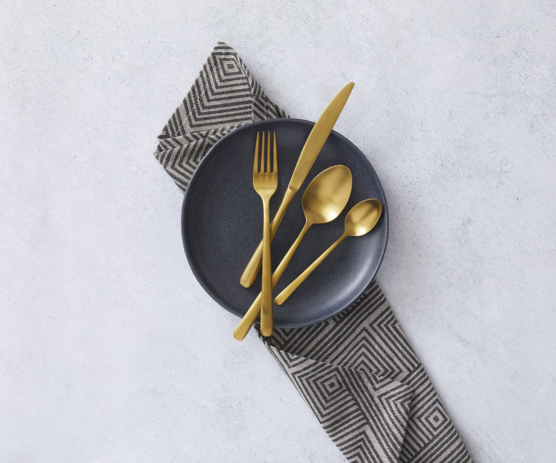 amalfi black and gold cutlery and plate on marble table