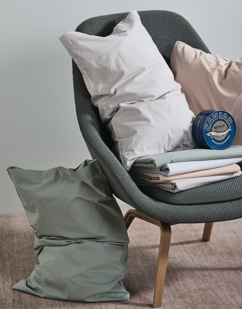 olive green armchair with green and pink pillow caes from in bed
