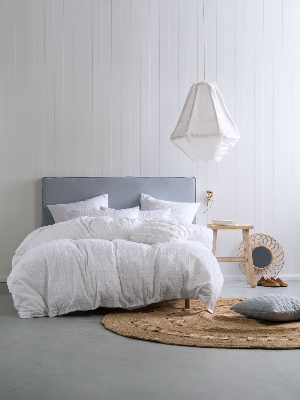 White Timber Panel Bedroom With Concrete Floor And Grey Upholstered  Headboard And Jute Rug