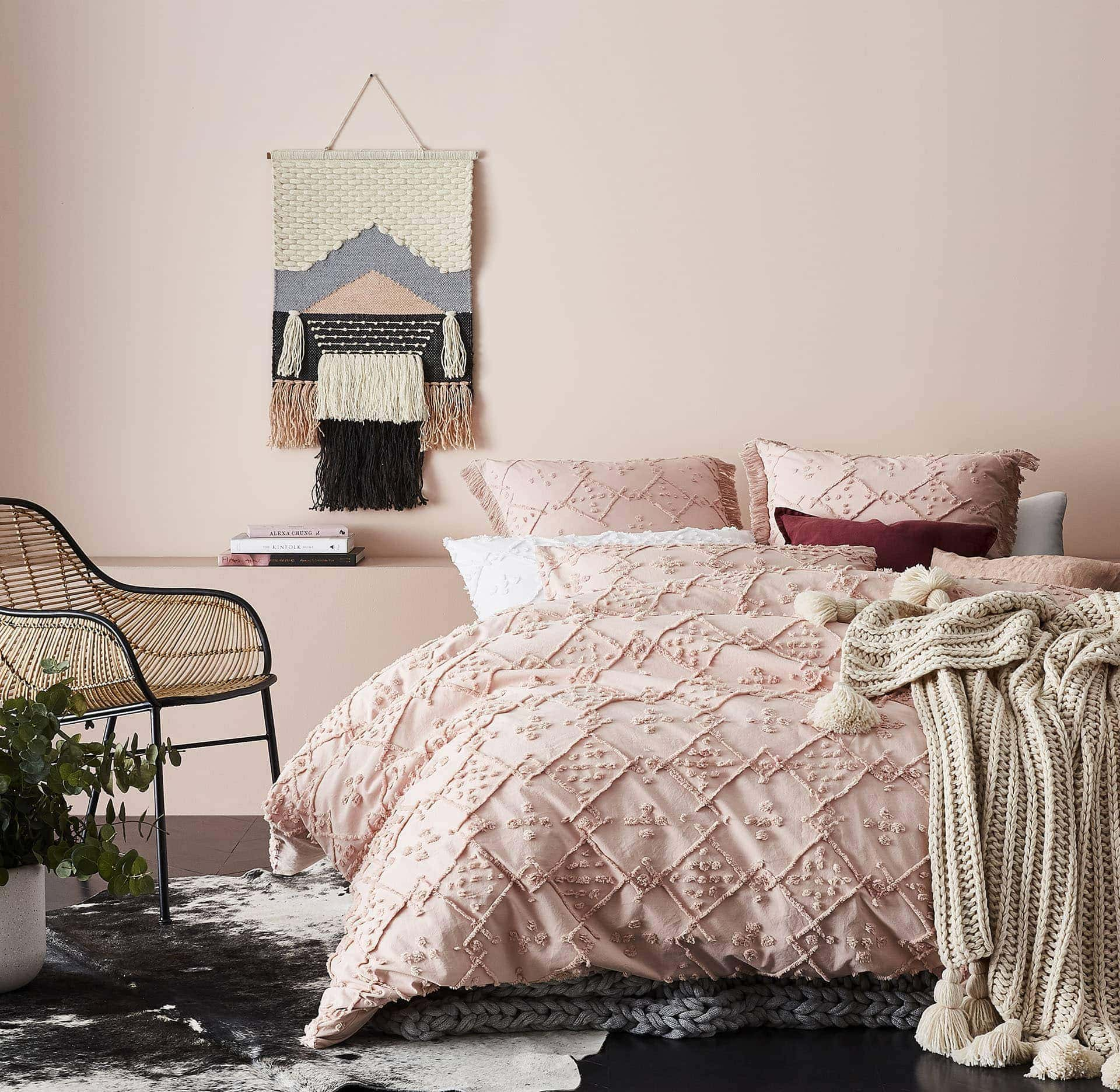 adairs pink bedding with diamond shapes and beige throw with tassels
