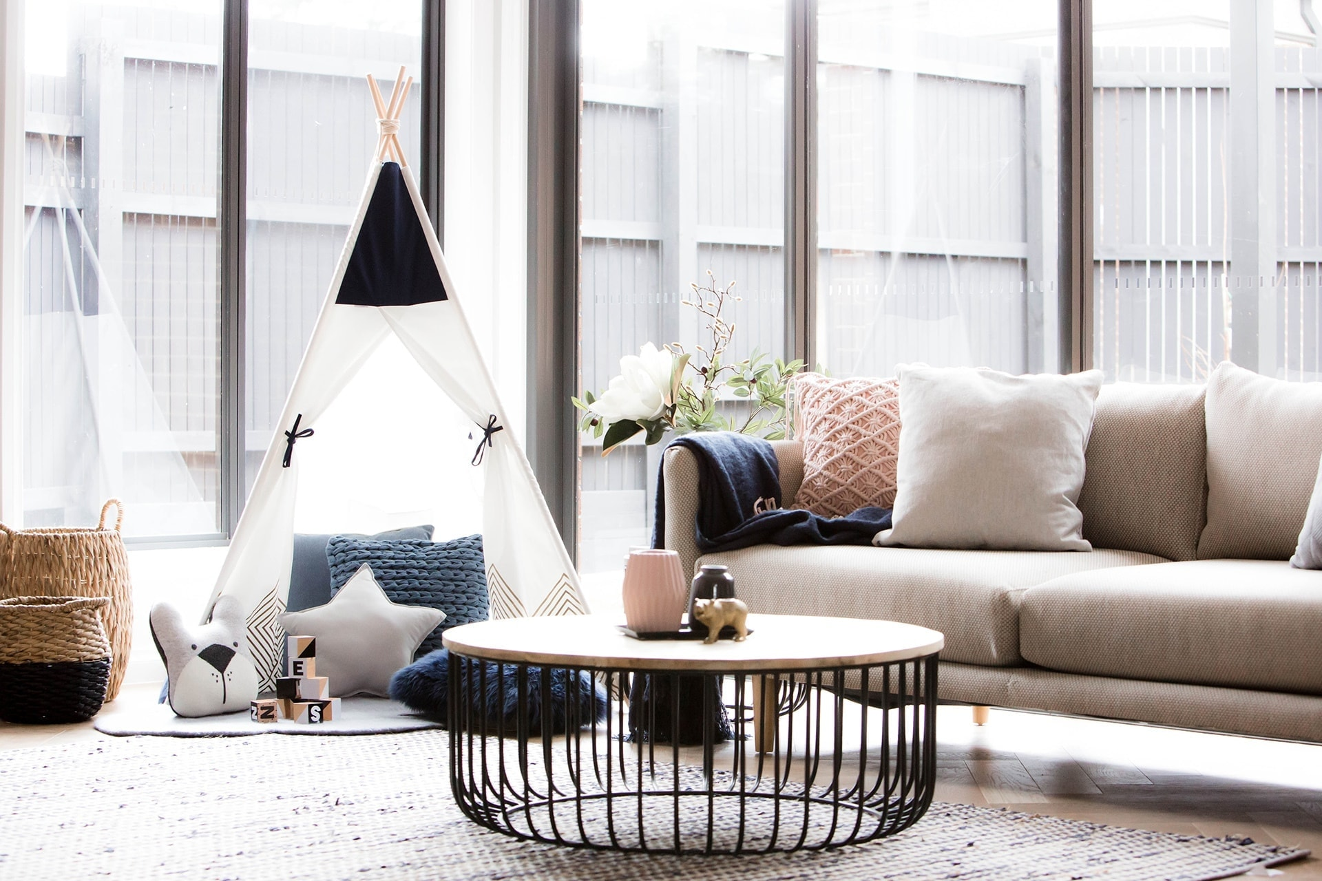 grey pink and blue living room with round globewest coffee table and kids teepee