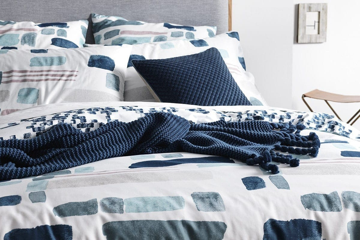 navy blue coloured cushions on white bed from sheridan