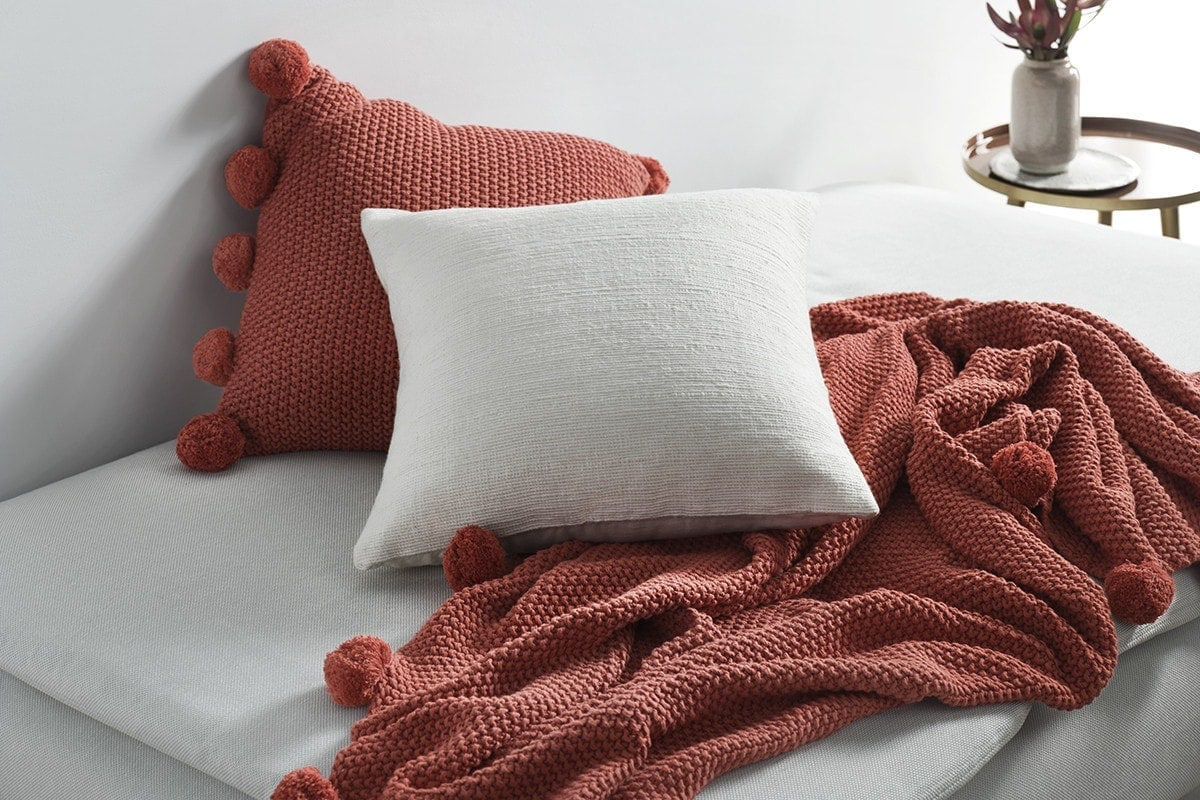 terracotta cushions from sheridan on soft grey bed