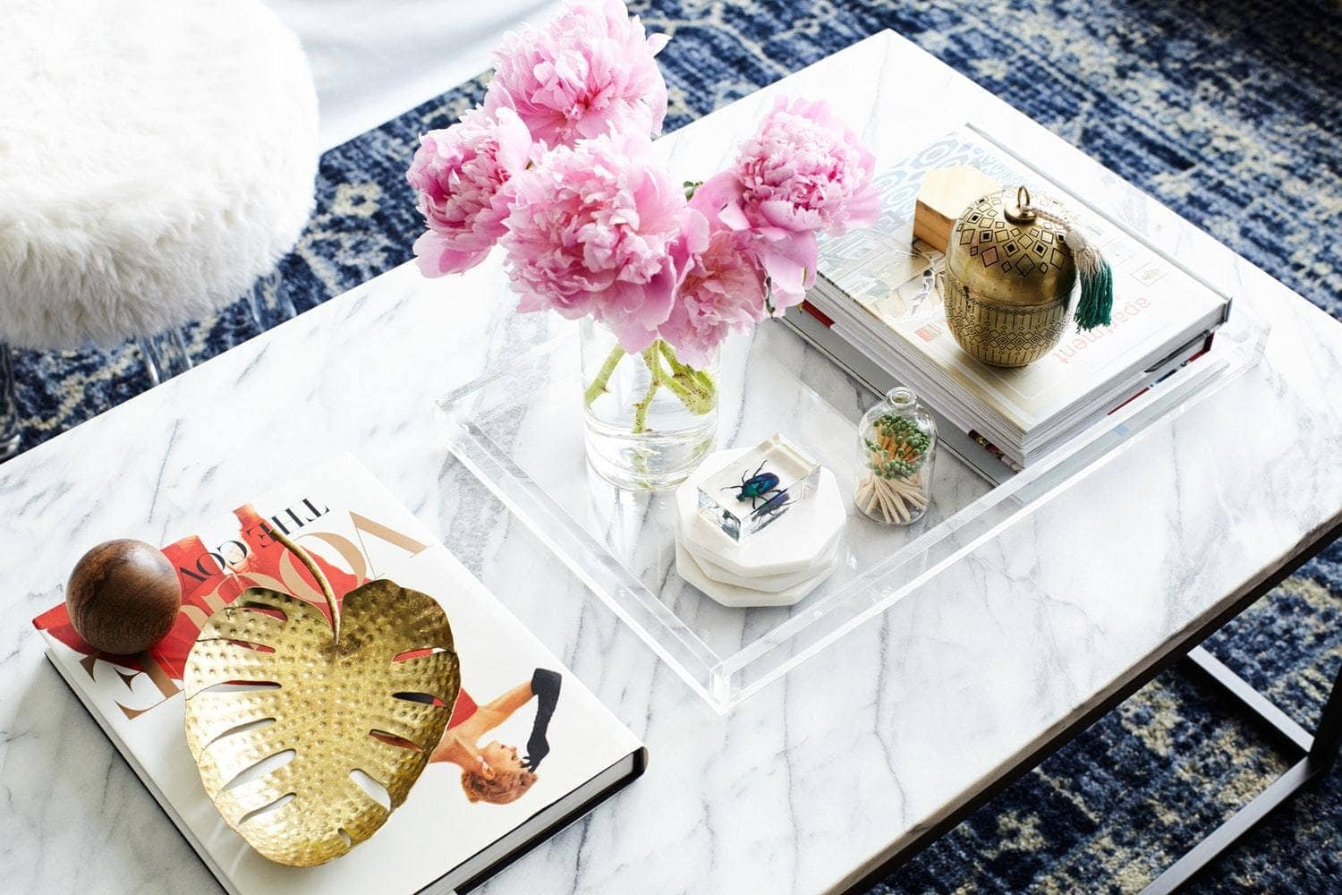 white marble coffee table with plastic tray and keepsakes