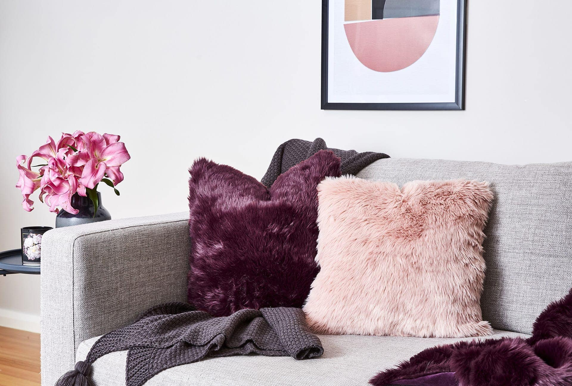 blush and purple faux fur cushions on grey sofa tlc interiors
