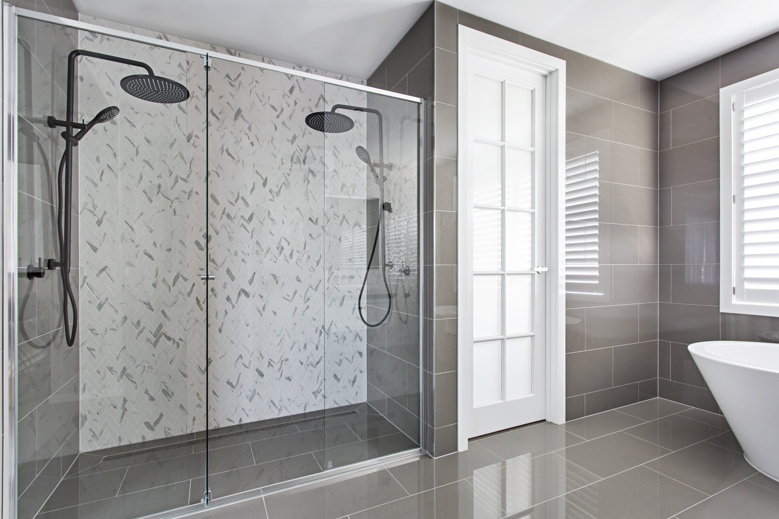 hamptons style bathroom double shower with black tapware and marble herringbone tiles