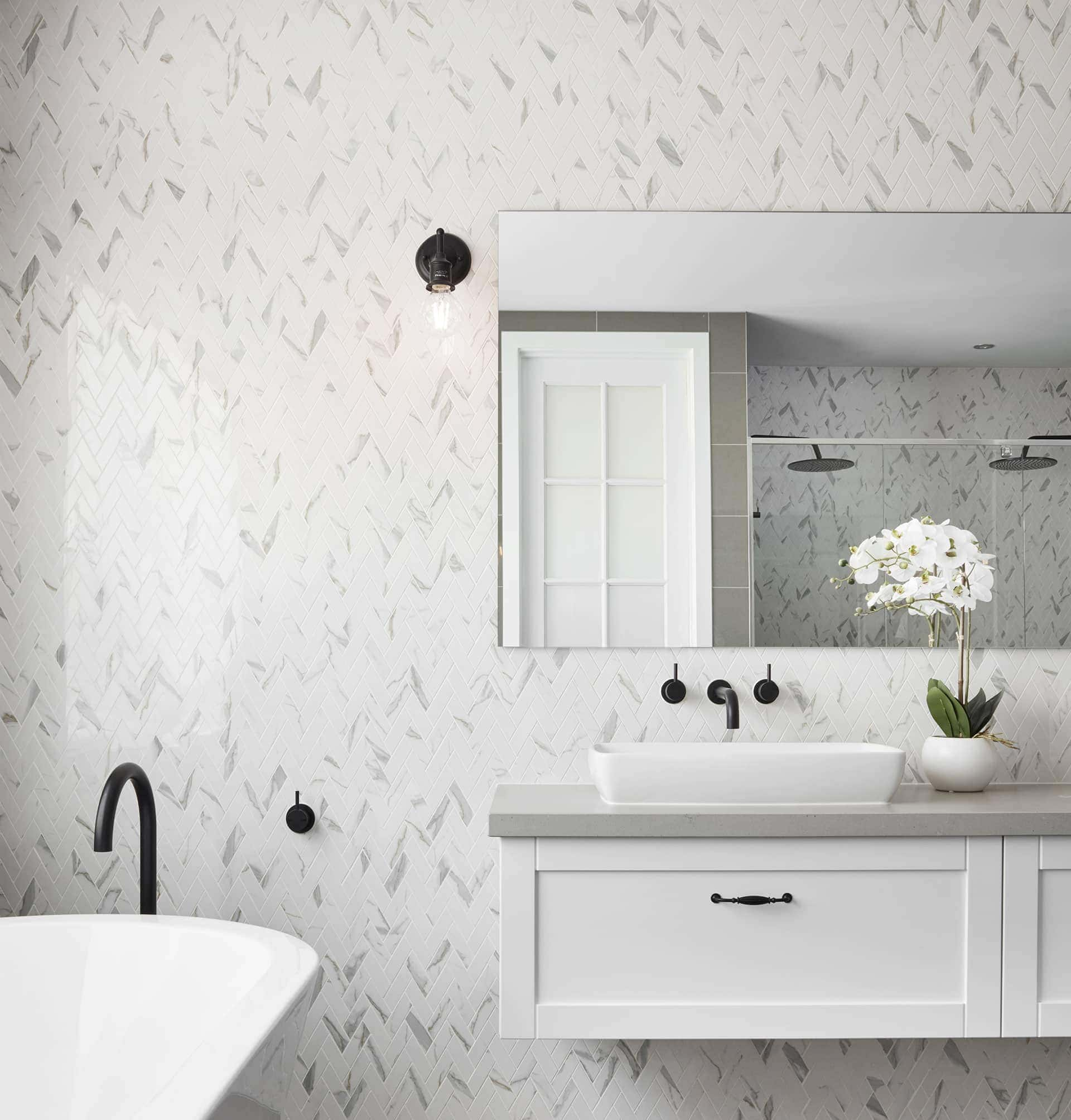 hamptons style bathroom with herringbone marble wall tiles and floating vanity with fake orchid