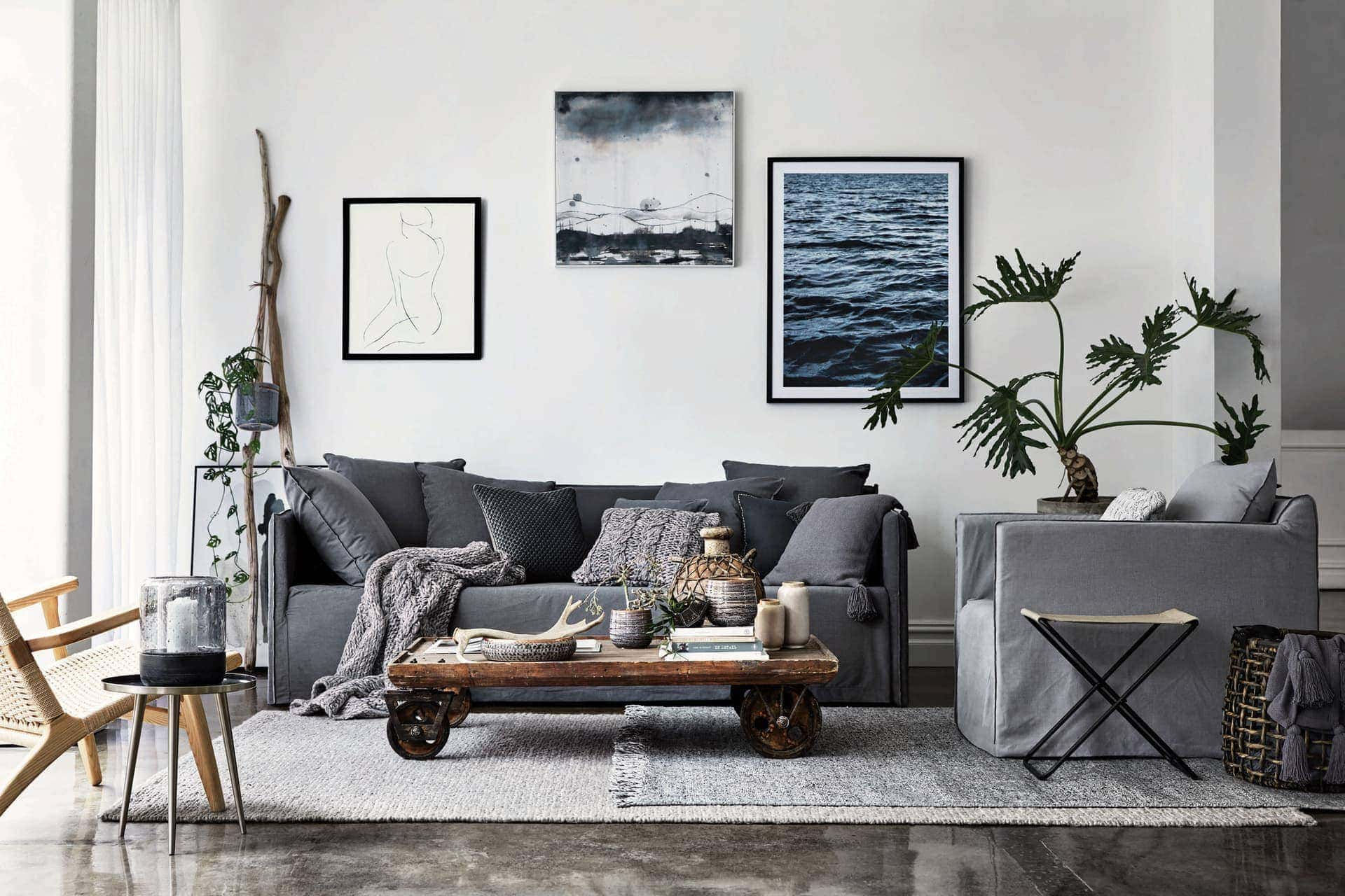 industrial coastal living room with grey slipcover sofa and industrial coffee table with wheels