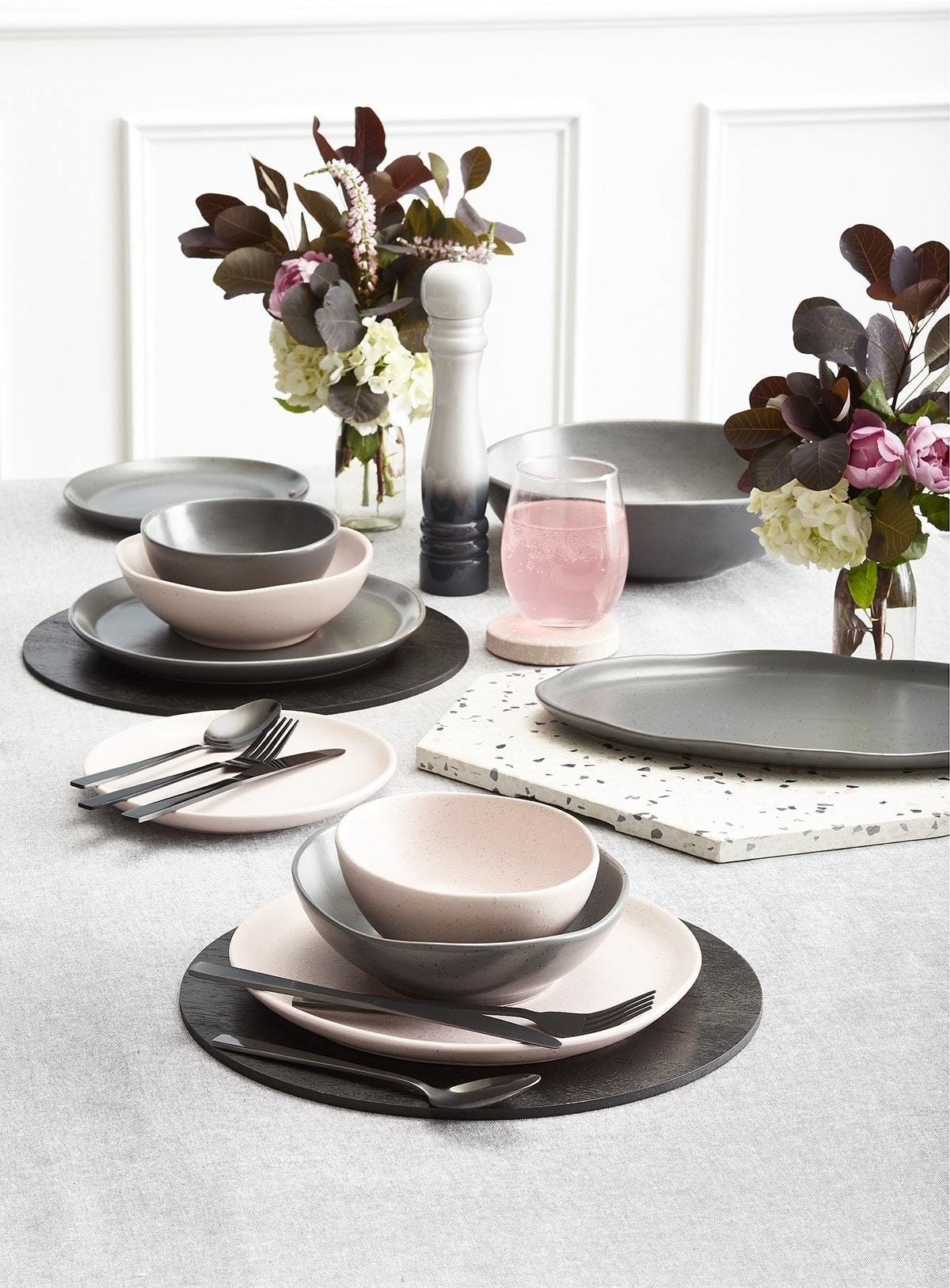 kmart pink dinnerware with black placemats and marble trivet