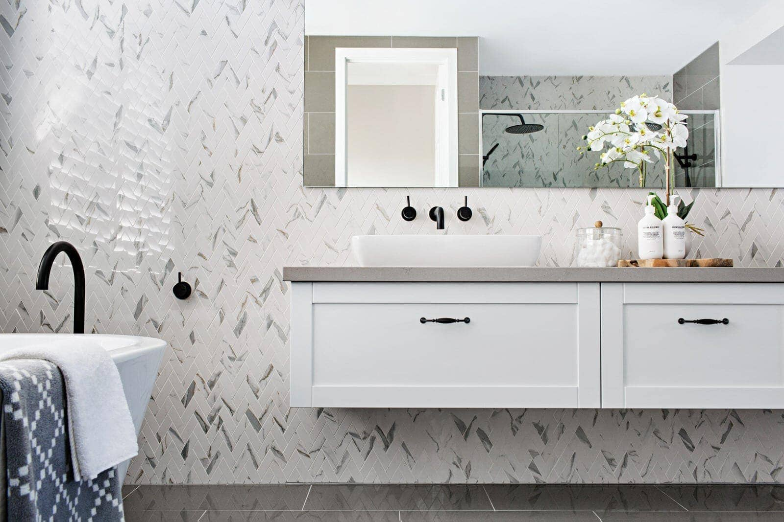 metricon hamptons style bathroom with marble herringbon tiles and floating vanity