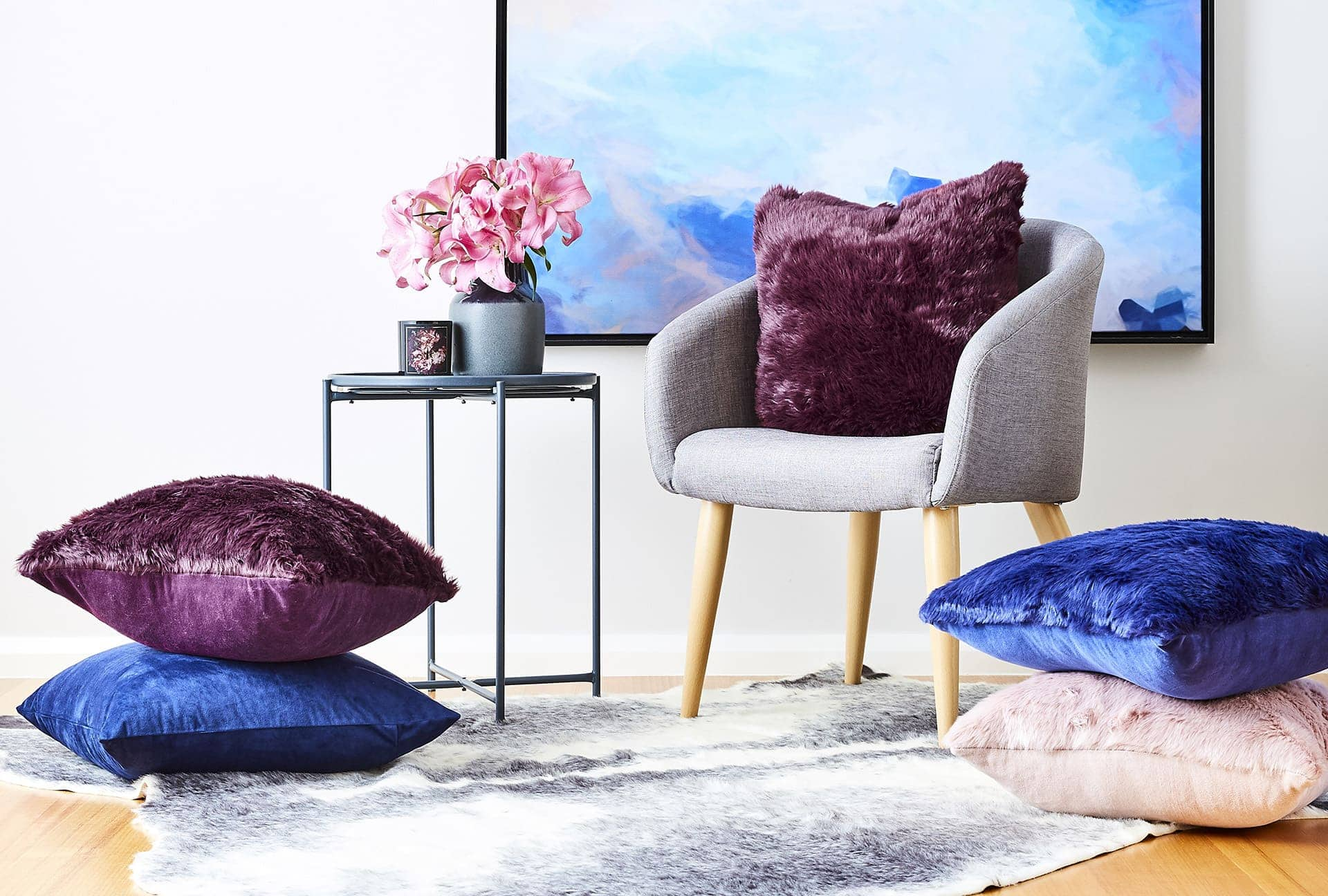 purple blue and pink cushions on kmart grey upholstered chair and faux fur rug