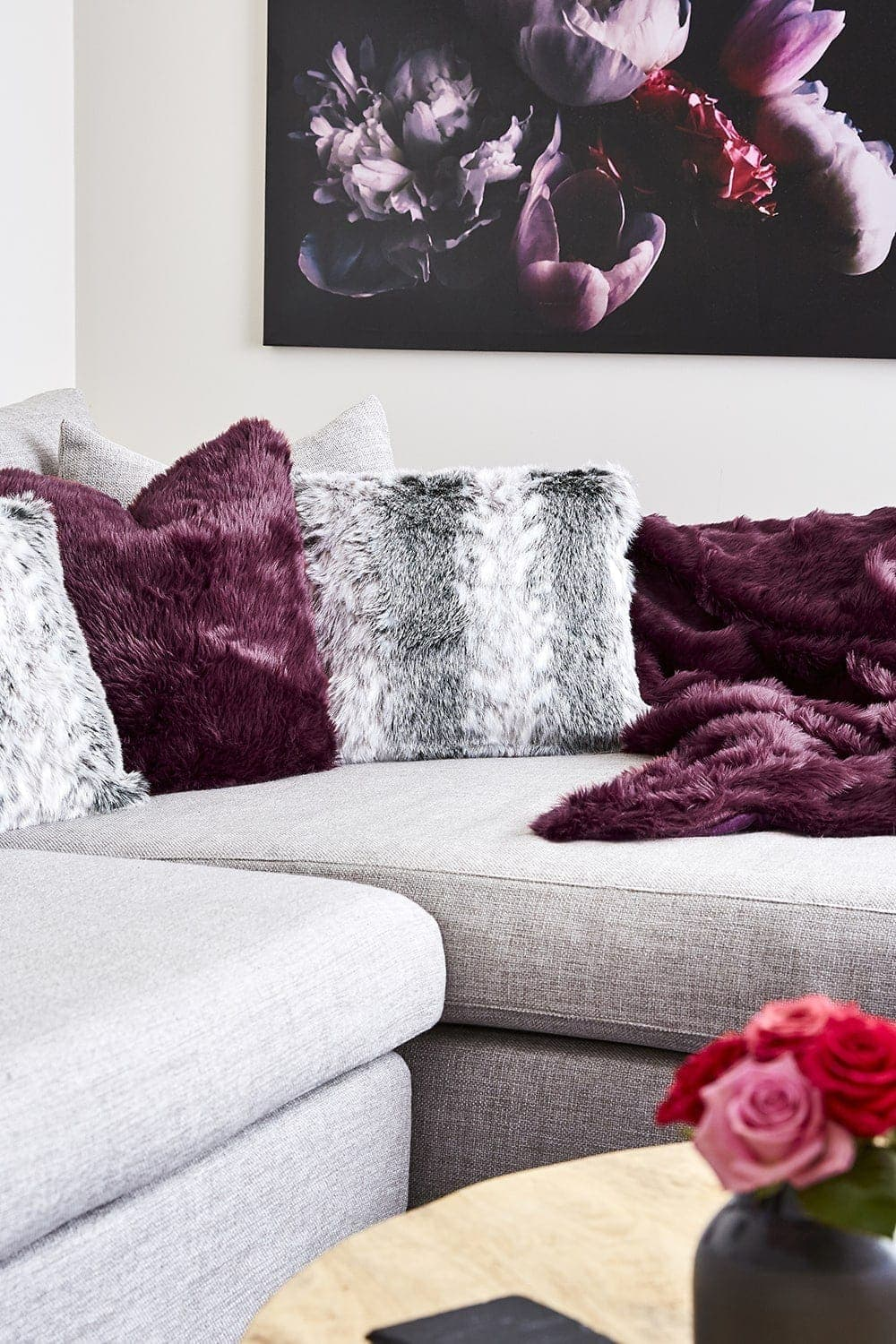 purple faux fur cushions and throw on light grey sofa and pink roses on coffee table