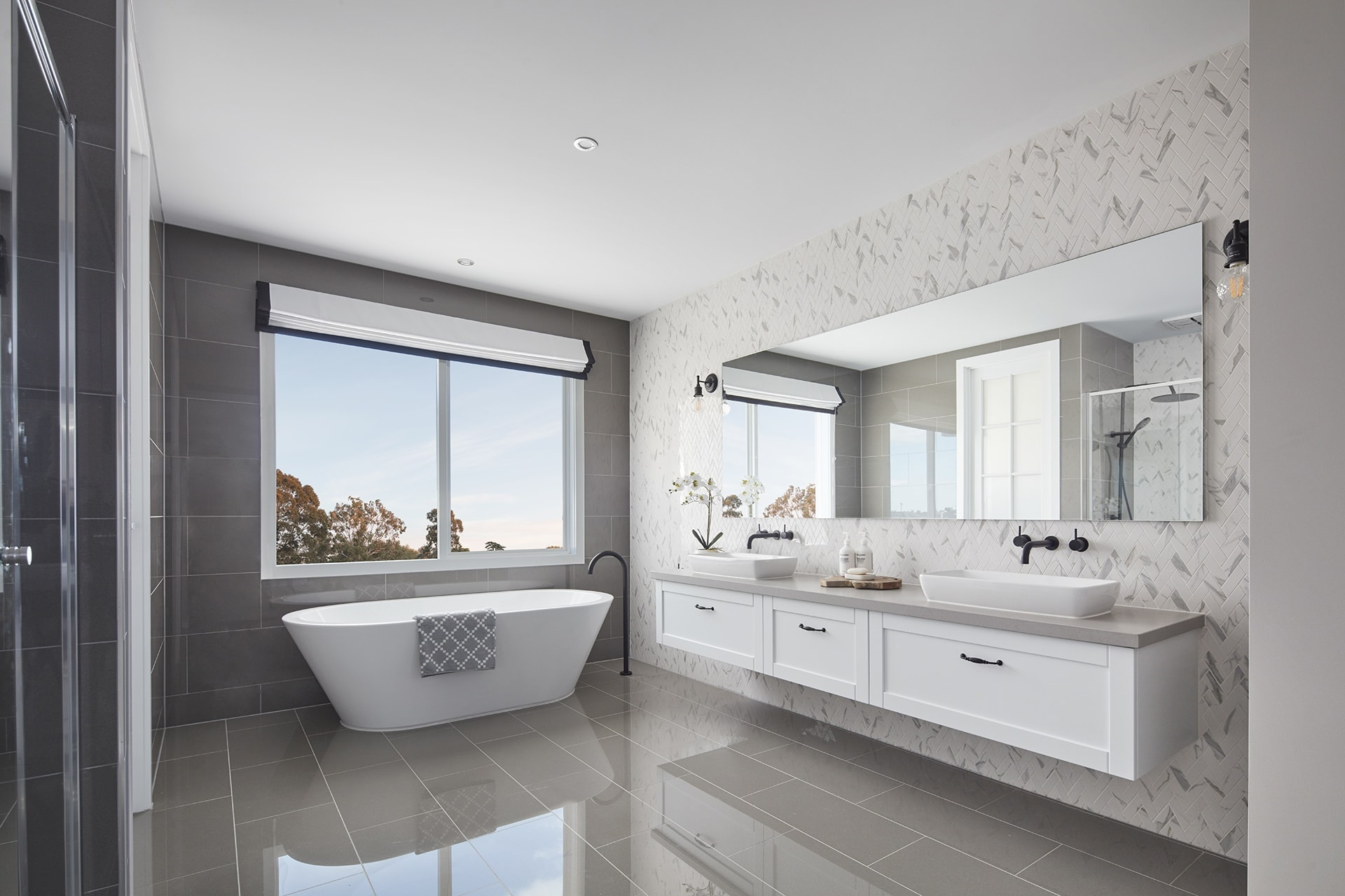 white and grey hamptons style bathroom with marble herringbone wall tiles and grey glass floor tiles