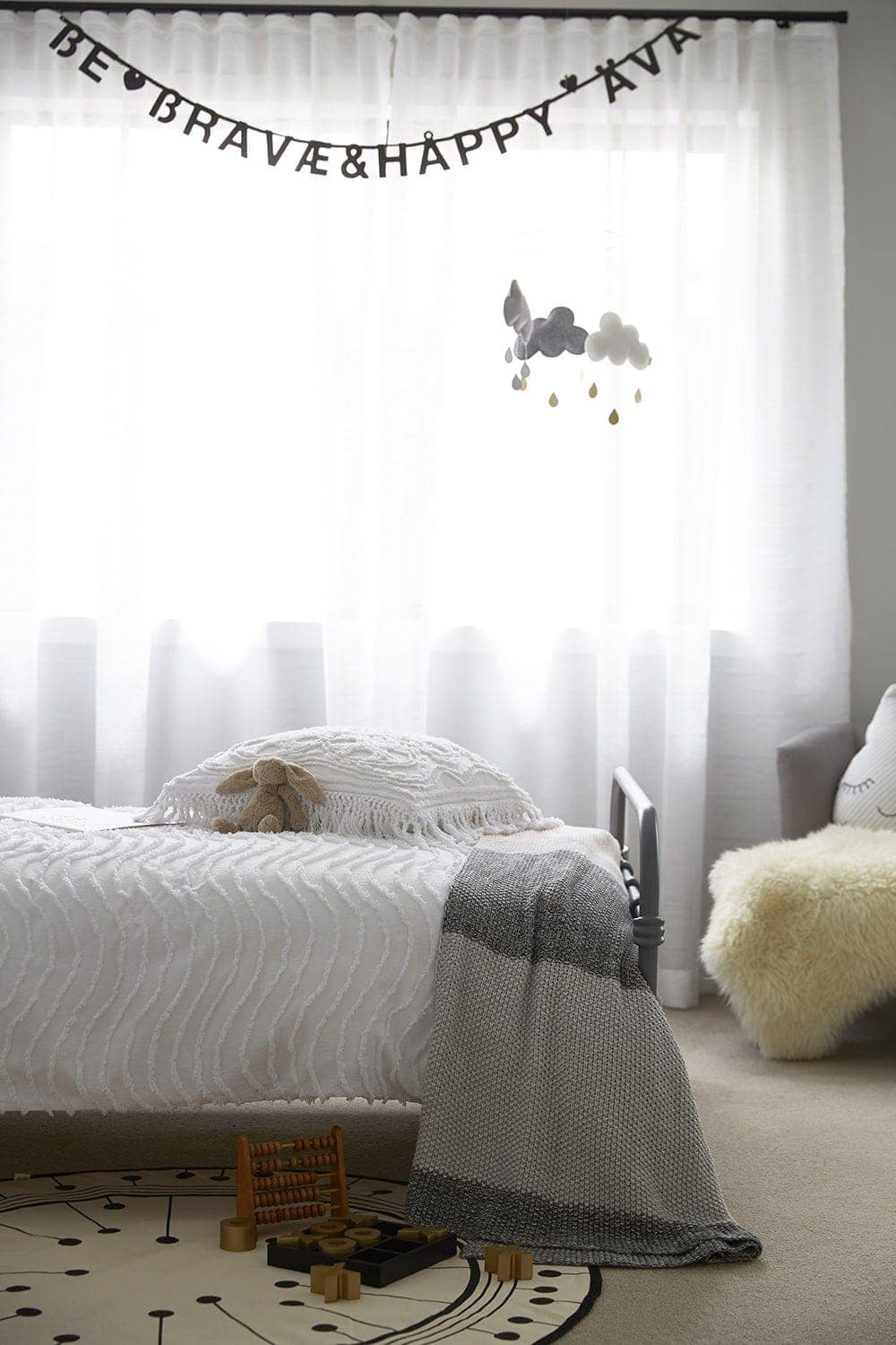 white sheer curtain in kids bedroom with white bedding