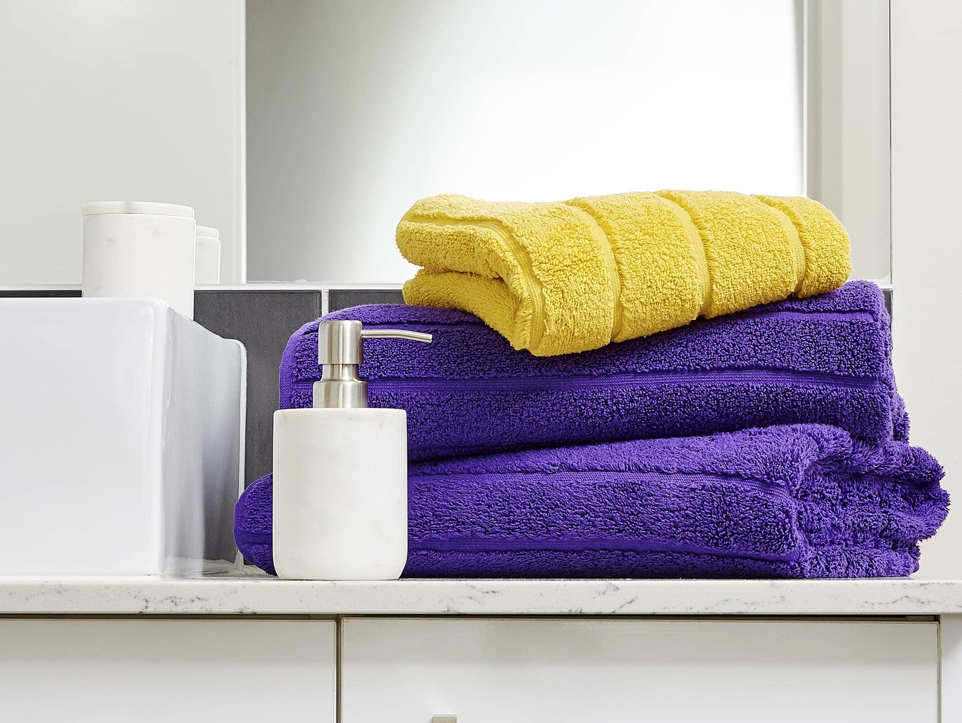 yellow and purple towels stacked with marble soap dispenser from lorraine lea