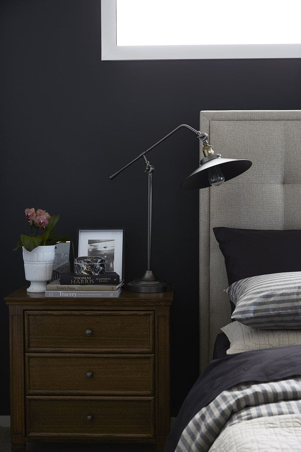 dark master bedroom wall with brown timber bedside table