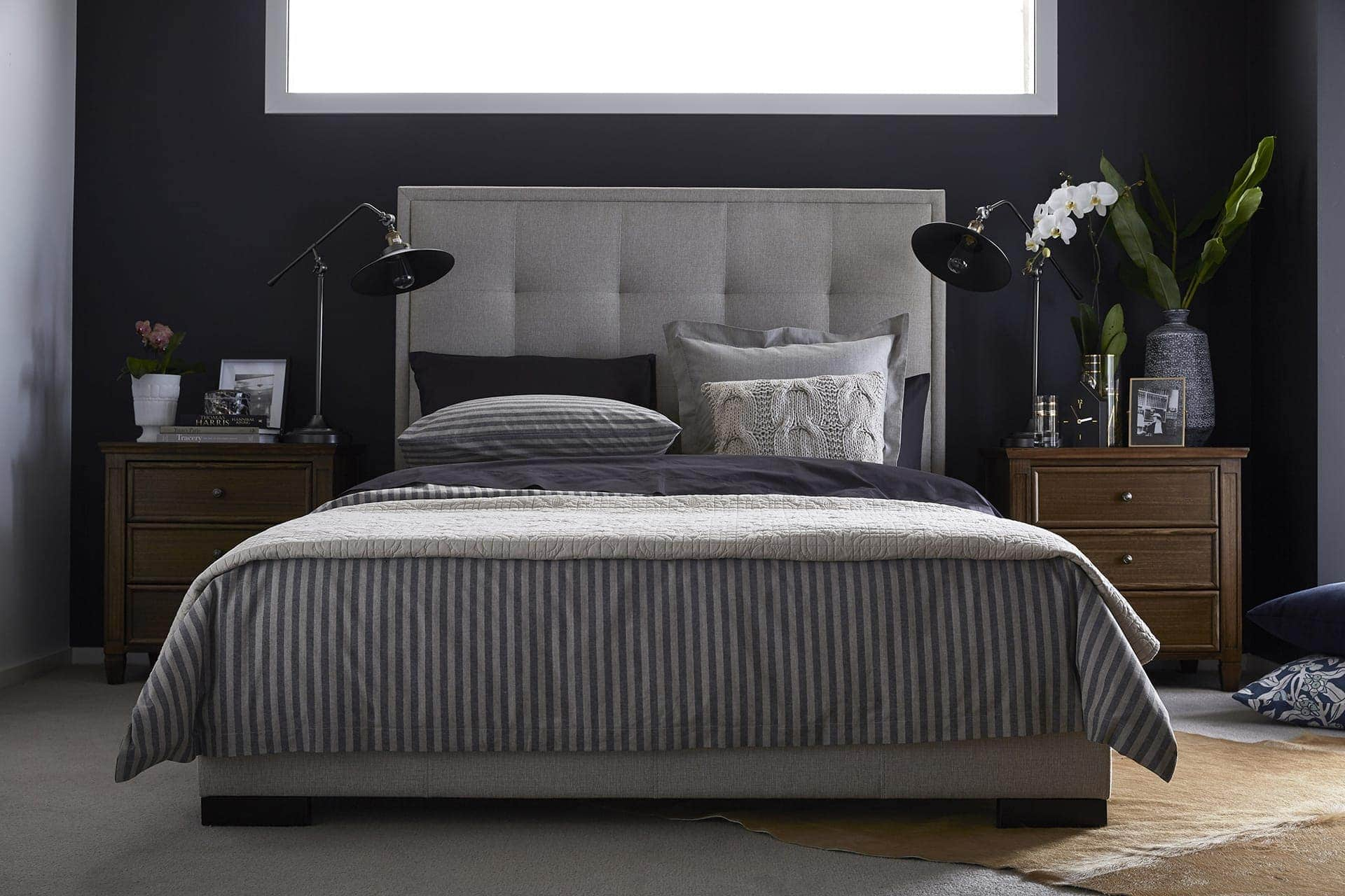 dark master bedroom with grey upholstered headboard