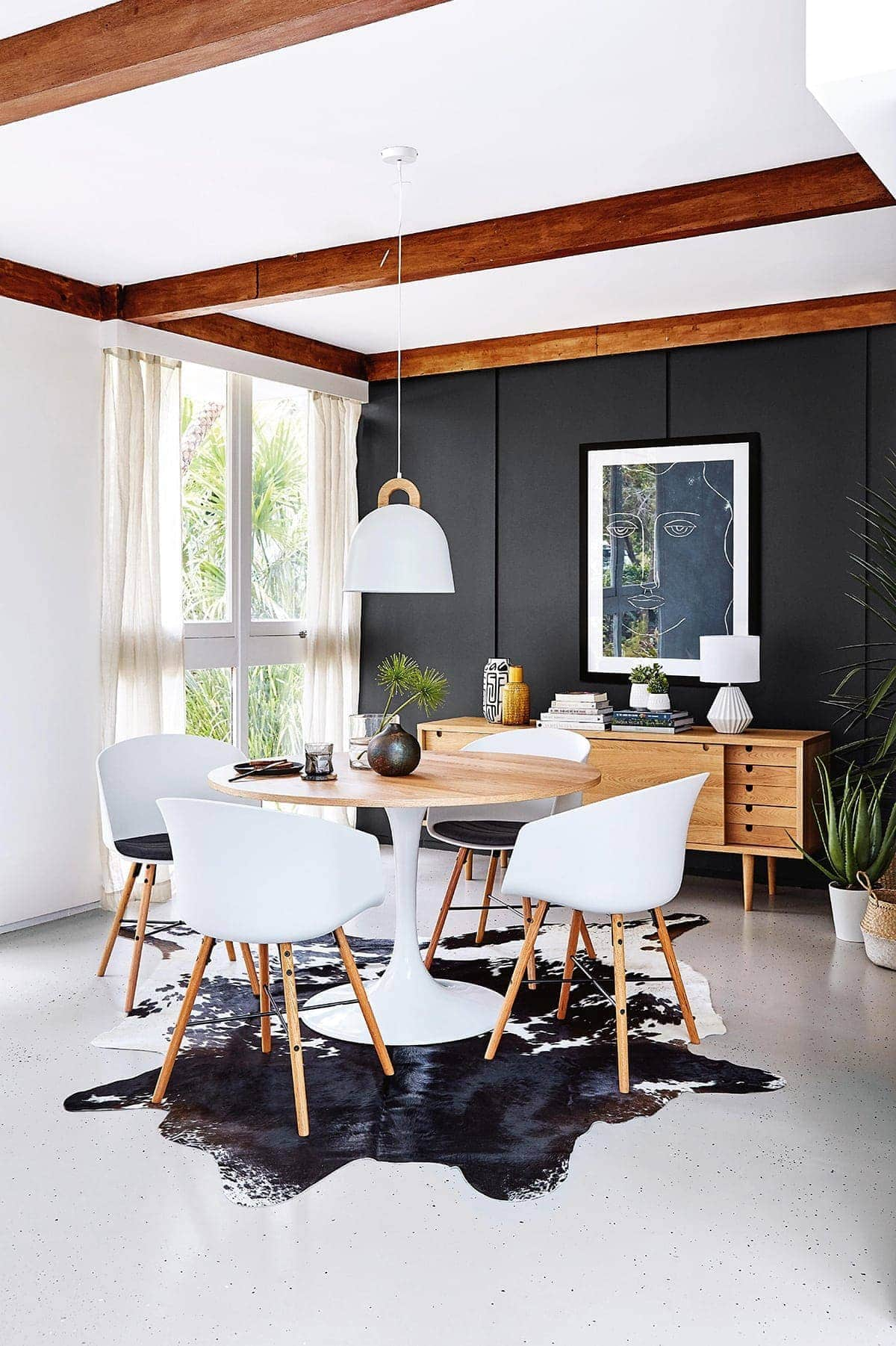 dark brown cowhide rug under white dining table from freedom