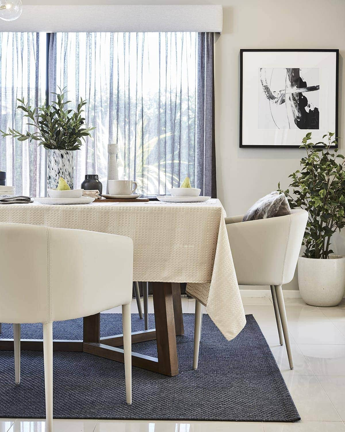 beige tablecloth on dining table with beige leather dining chairs
