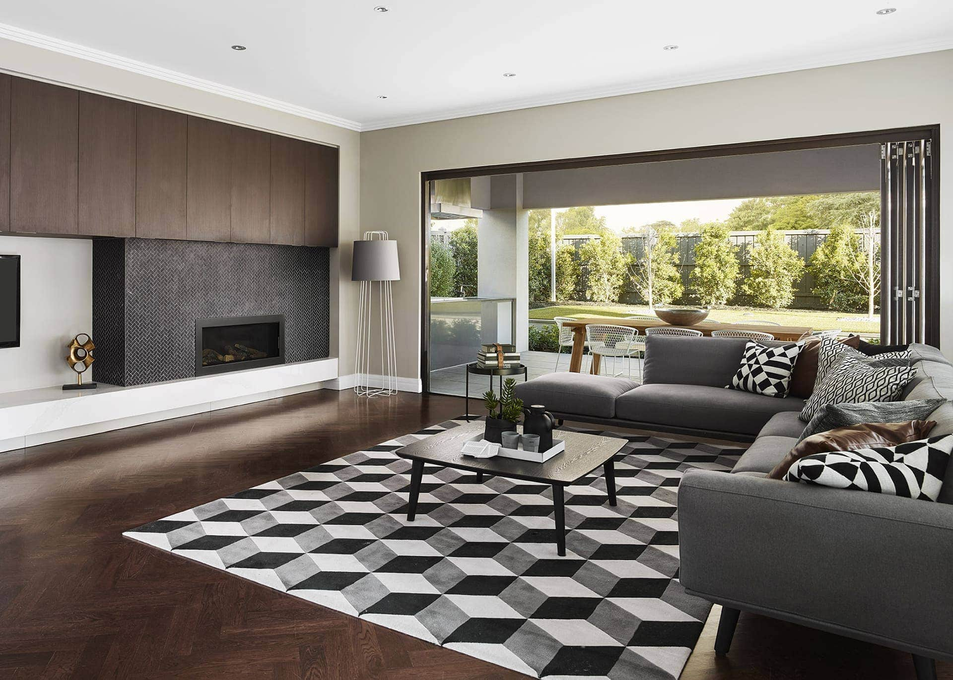 black and white geometric rug in living room with dark herringbone timber floor
