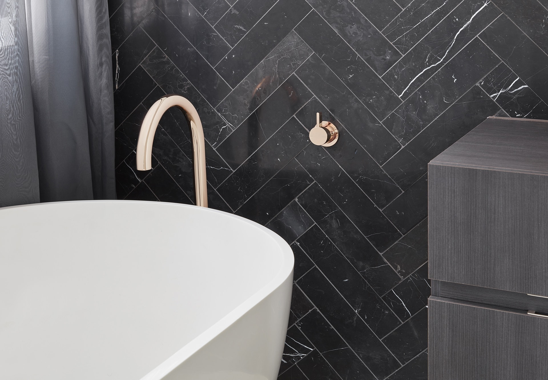 black marble herringbone tile in luxe bathroom with gold tapware