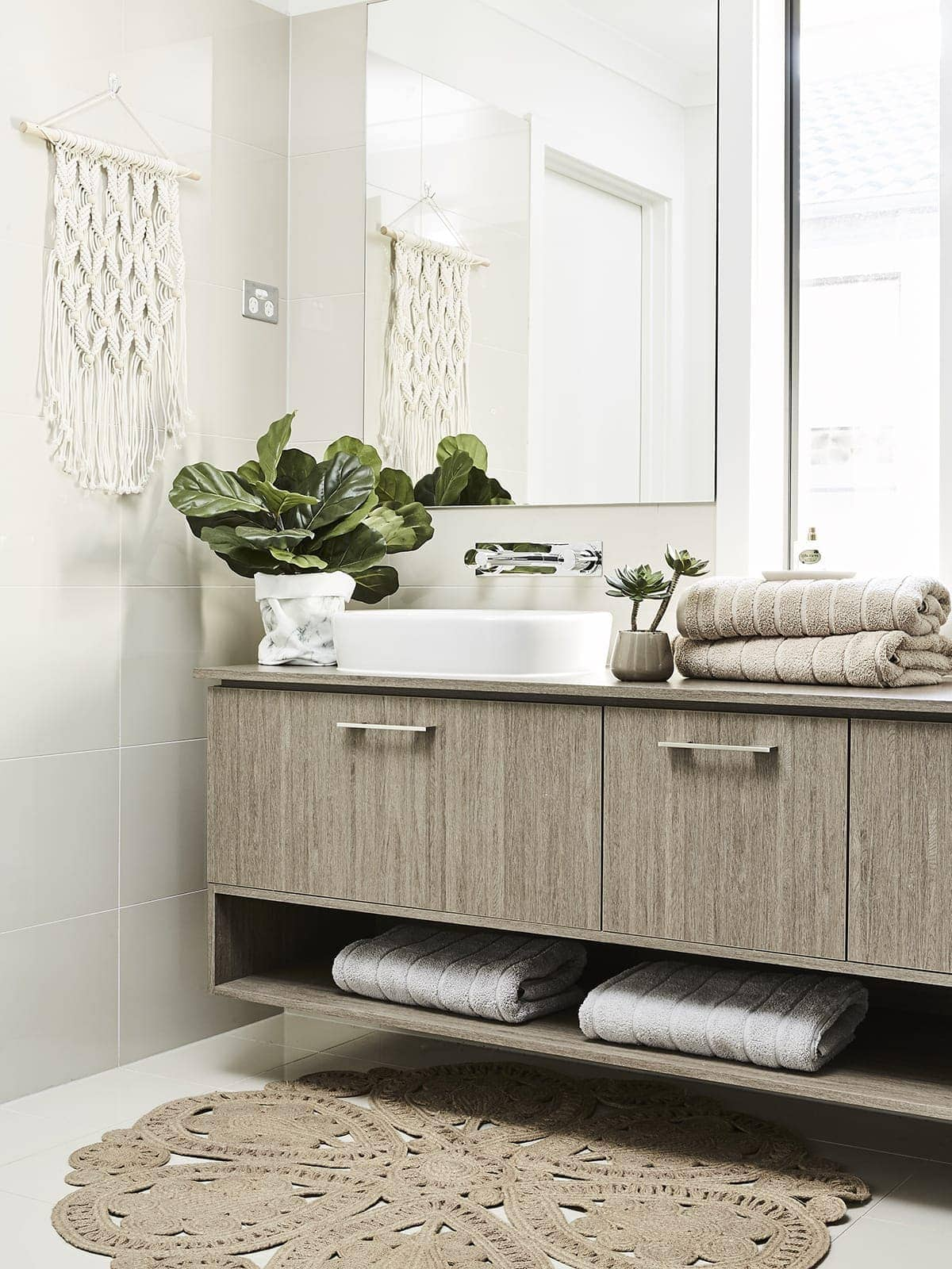 brown timber bathroom with round jute rug on floor and macrame wall hanging on bathroom wall